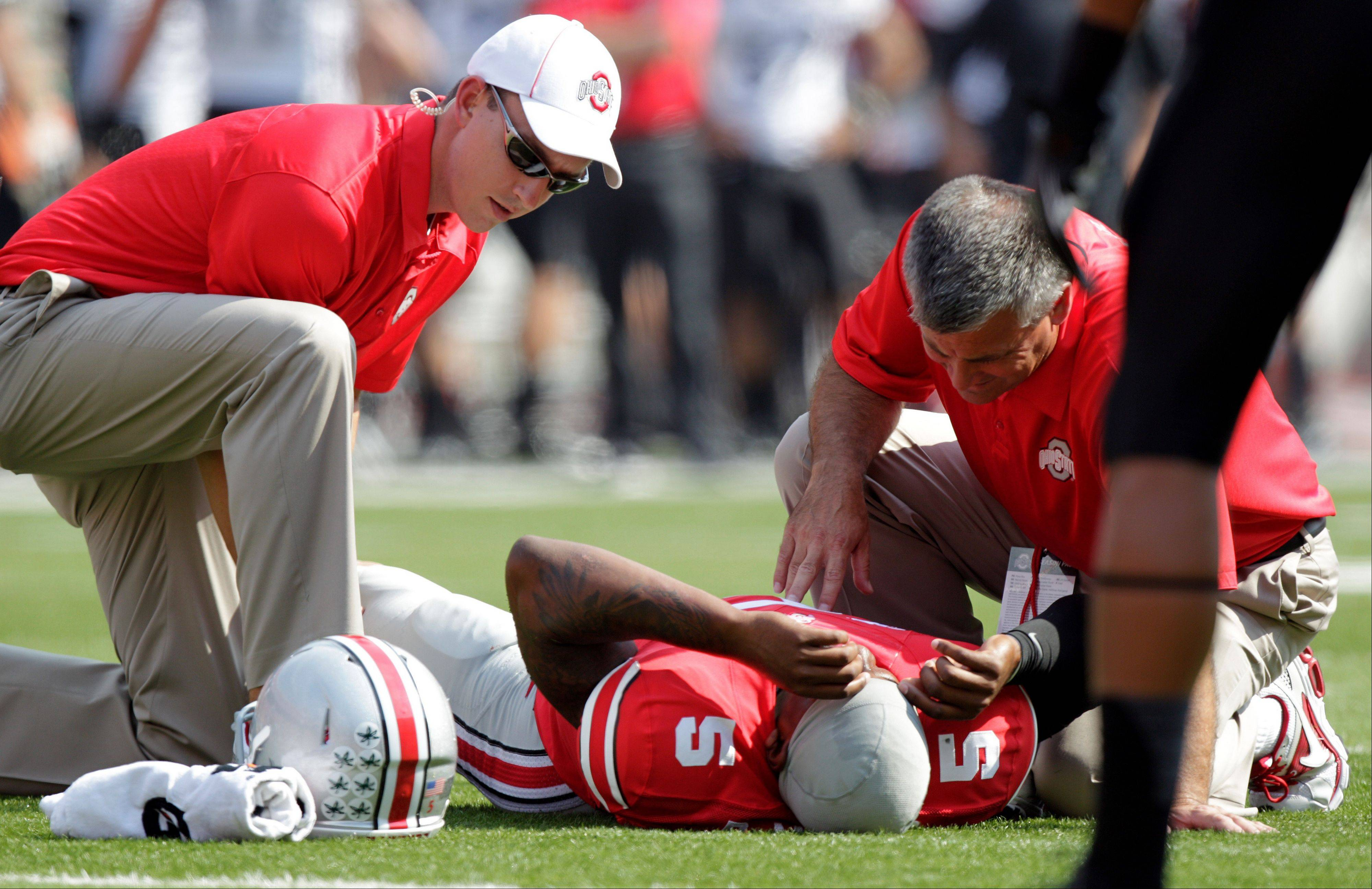 Ohio State trainers tend to quarterback Braxton Miller after he was injured during Saturday's home game against San Diego State.