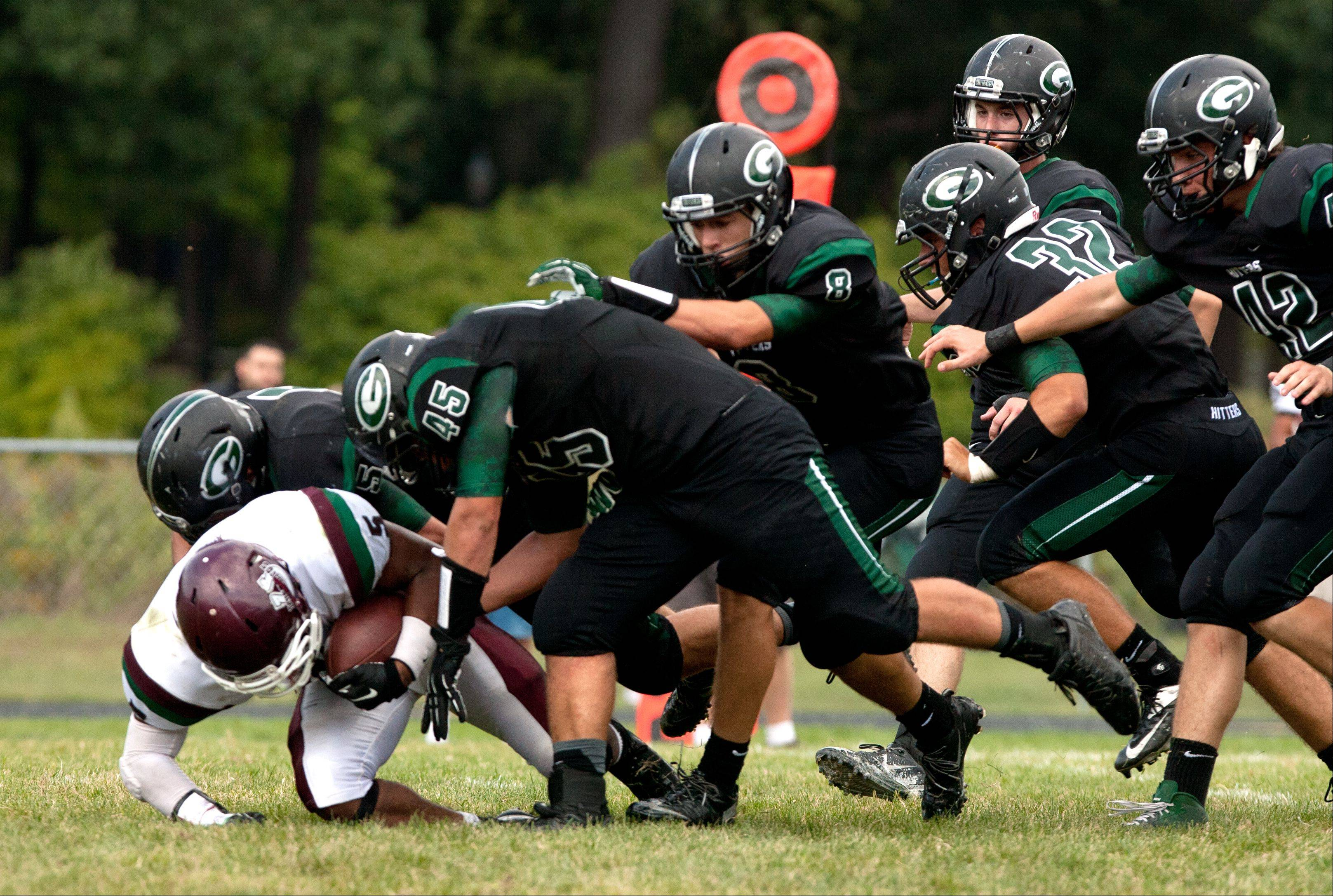 Glenbard West's defense swarm Morton's M. Hester during Saturday's football game.