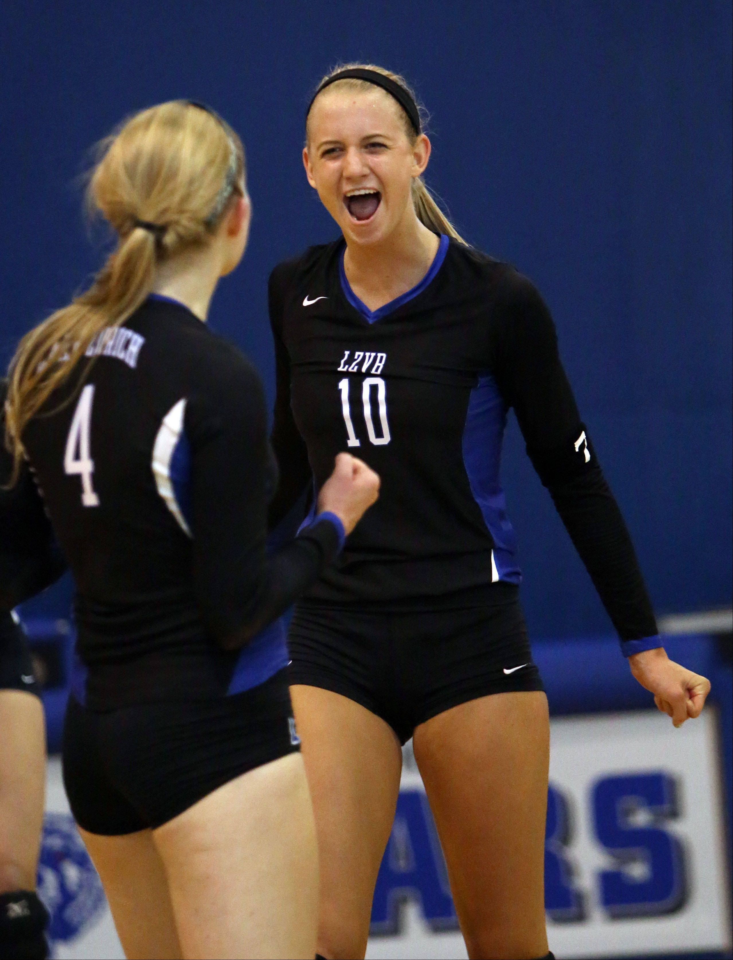 Lake Zurich's Kristen Walding, right, celebrates with teammate Kiley McPeek after winning a point against Carmel Tuesday in Lake Zurich.