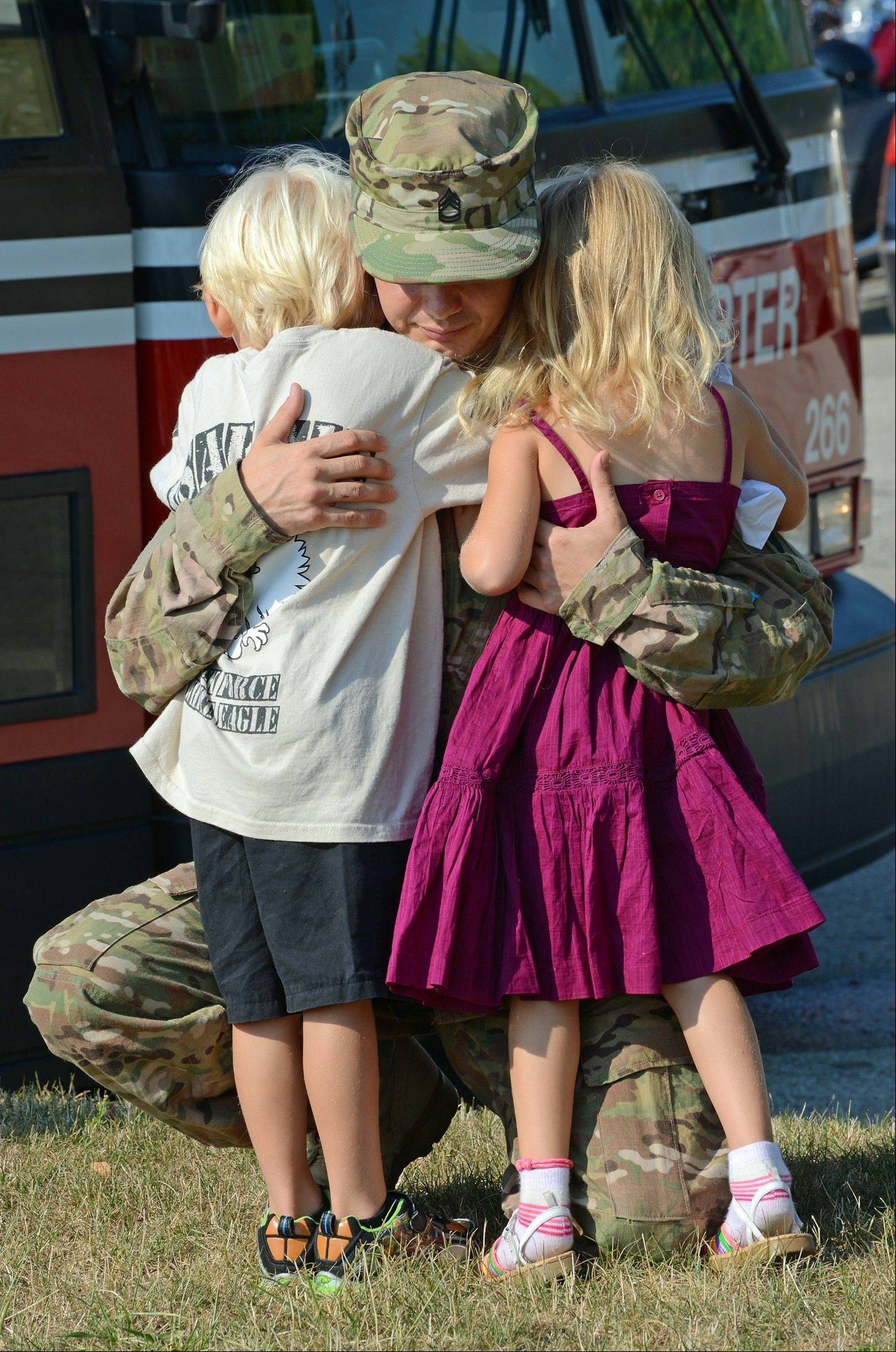 Illinois Army National Guard Staff Sgt. Richard Hollinshead of Williamsville hugs his crying twins, Lucas and Makaylea, 4, on Tuesday before prior leaving the armory in Bloomington for a deployment in Afghanistan.
