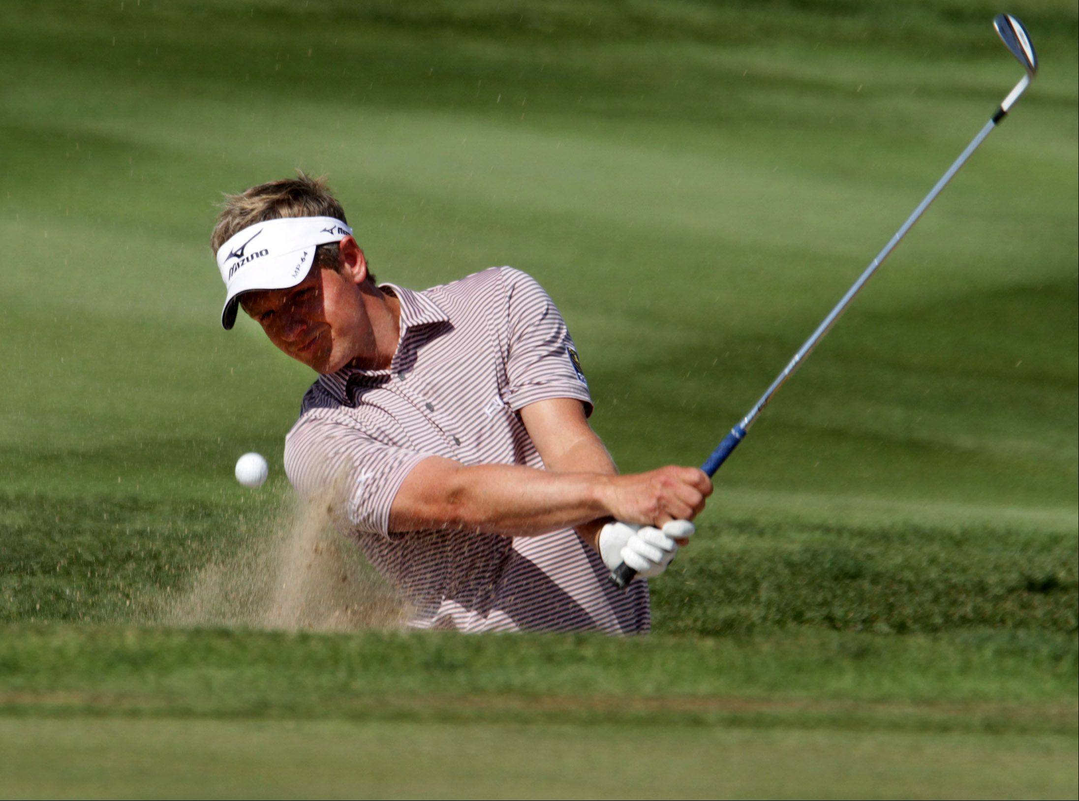 Luke Donald practices swinging from sand on the putting green Tuesday.