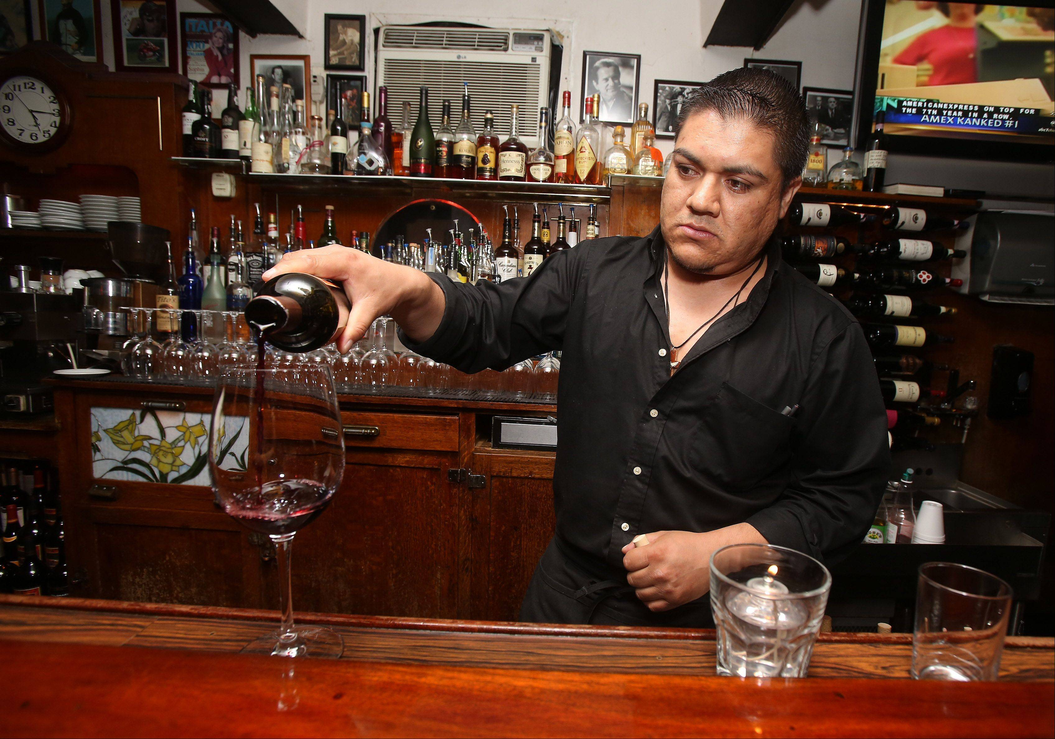 Bartender Joel Gaytan pours a glass of wine in the bar at DiPiero's Ristorante in Lake Zurich.