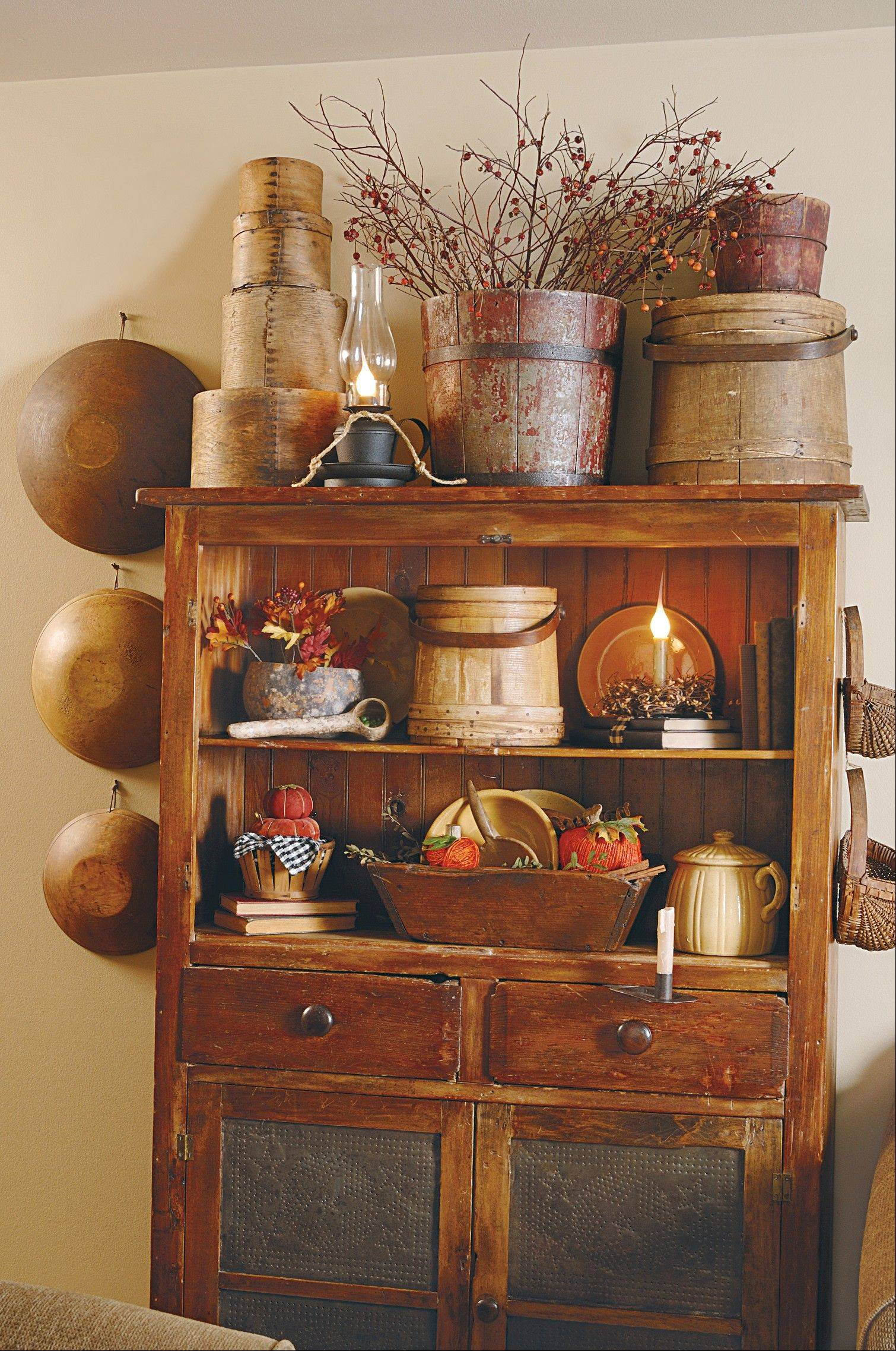 Illuminated by an oil lamp, an assortment of wood bowls, buckets, firkins, baskets and boxes keep the scene interesting in and around this cabinet.