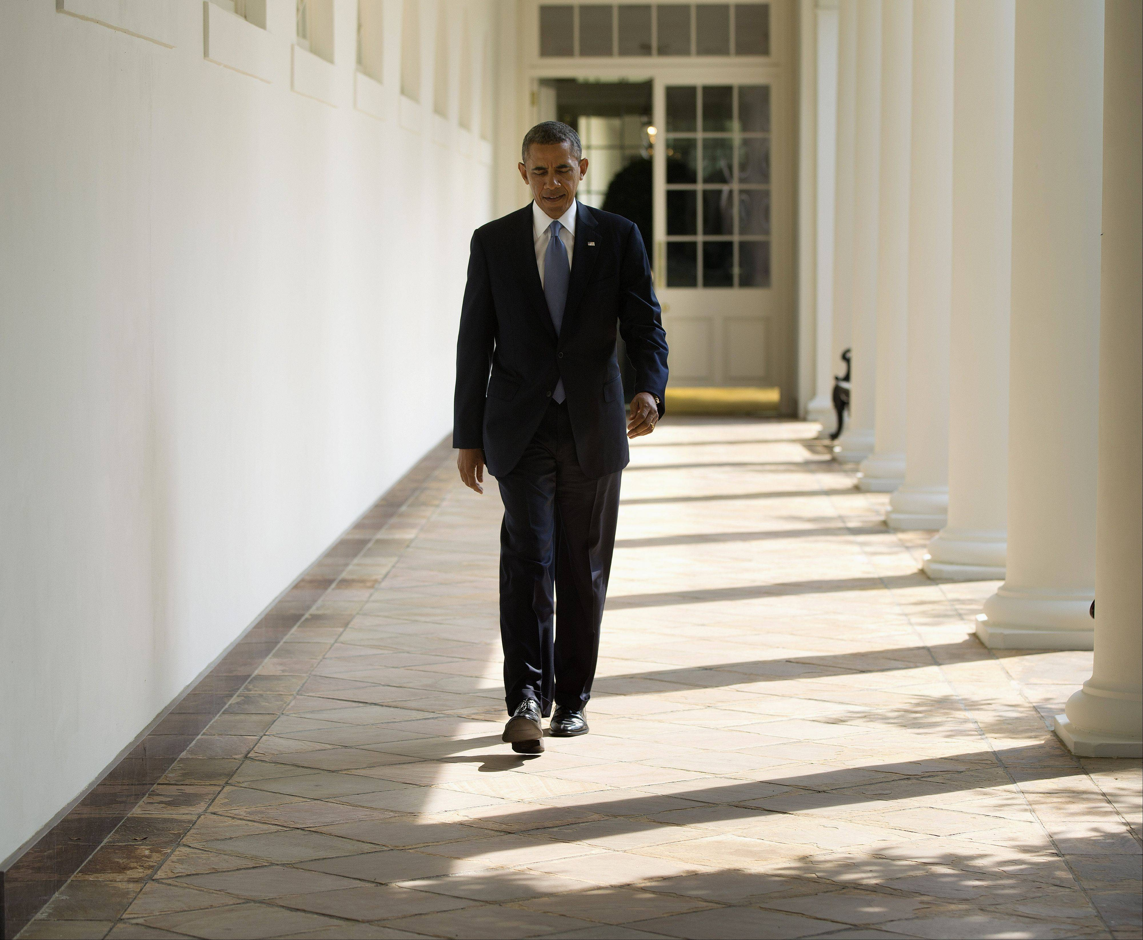 President Barack Obama walks along the West Wing Colonnade toward the Oval Office of the White House in Washington, ahead of his daily briefing Tuesday. Obama will deliver a speech on Syria from the East Room in an address to the national this evening.
