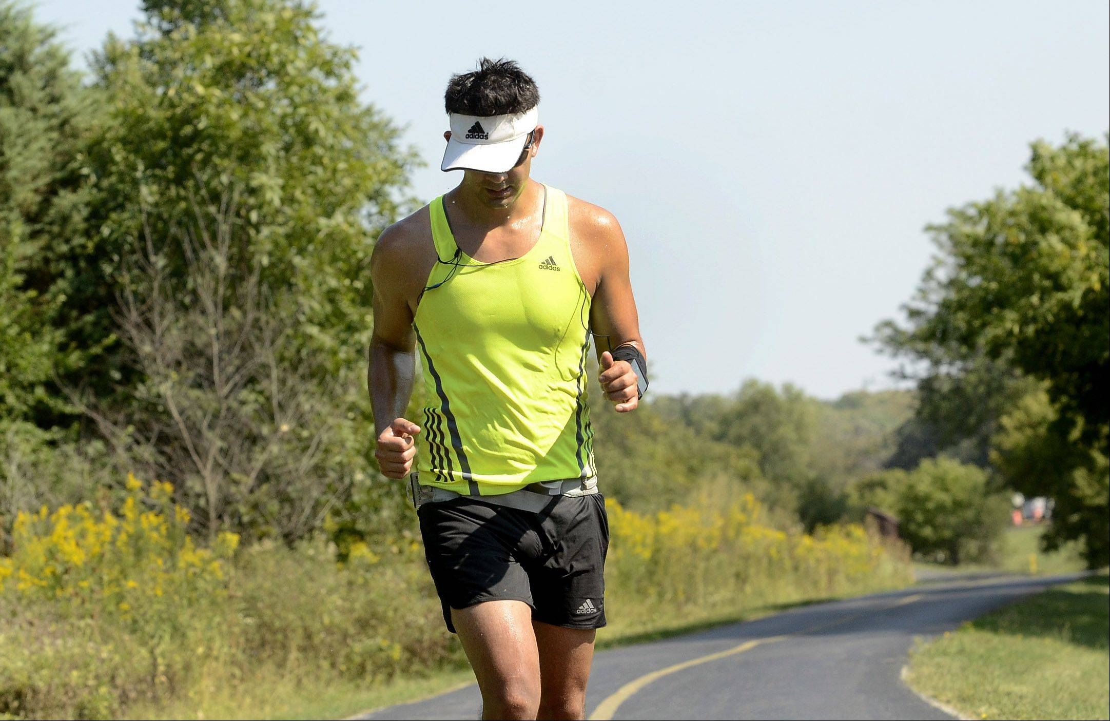 Despite record-tying heat, Michael Rosales of Hoffman Estates took to the paths in Busse Woods to train for the upcoming Chicago Marathon. He runs carrying plenty of water and hydrates constantly in this late summer heat.