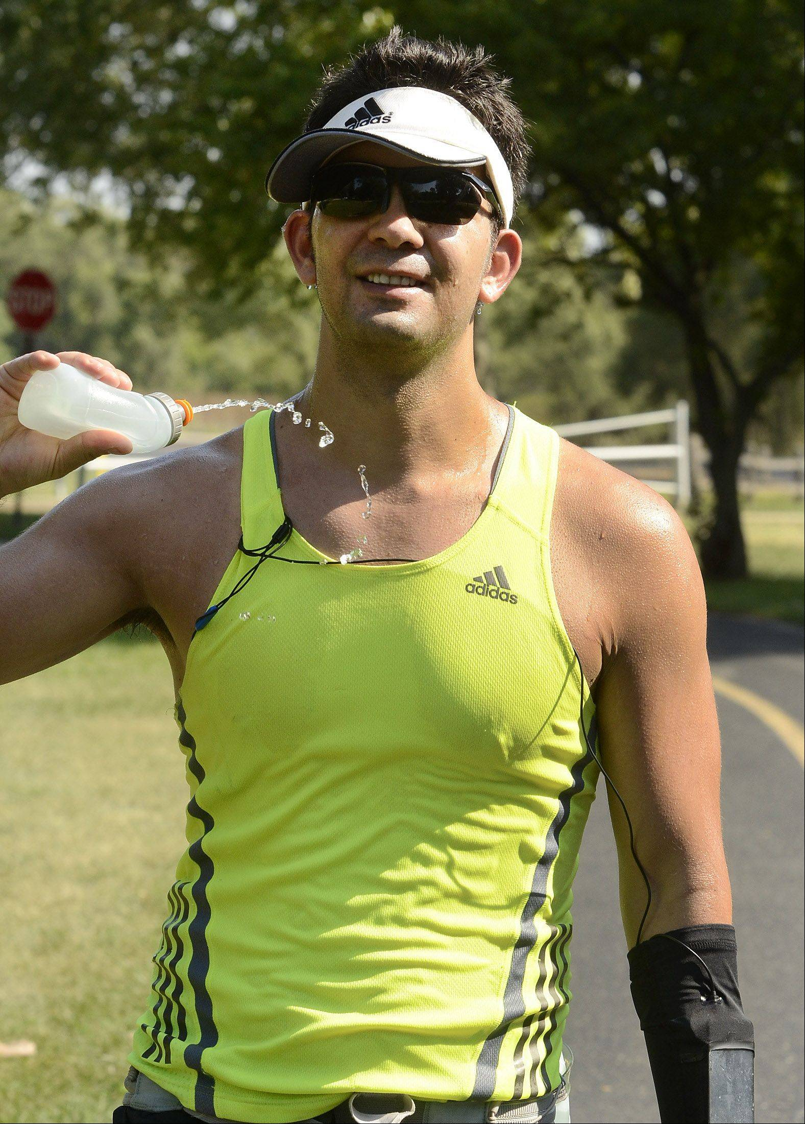 Despite record-tying heat, Michael Rosales of Hoffman Estates took to the paths Tuesday in Busse Woods to train for the upcoming Chicago Marathon. He runs carrying plenty of water and hydrates constantly in this late summer heat.
