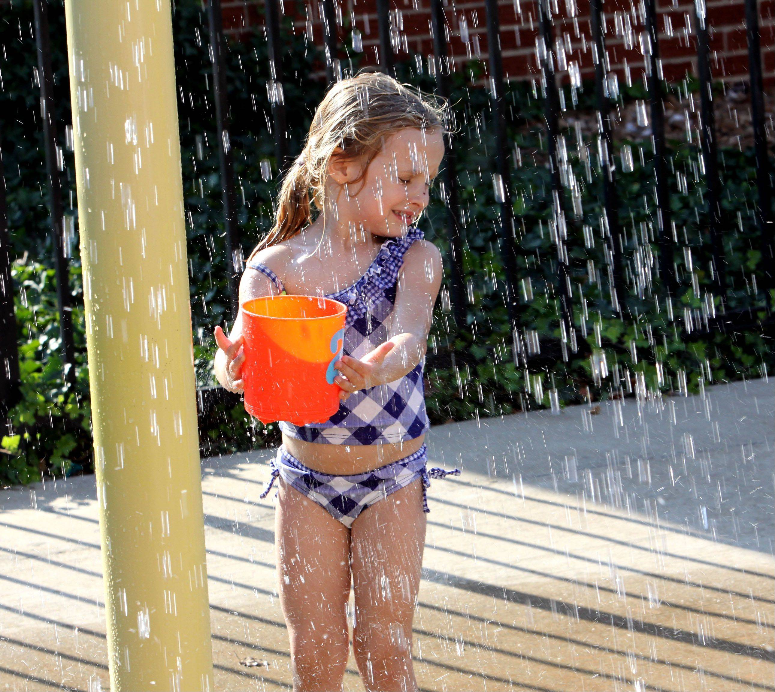 Madeline Deeke, 4, cools off from the heat and fills her bucket at the Water Spray Park in Lombard on Tuesday.