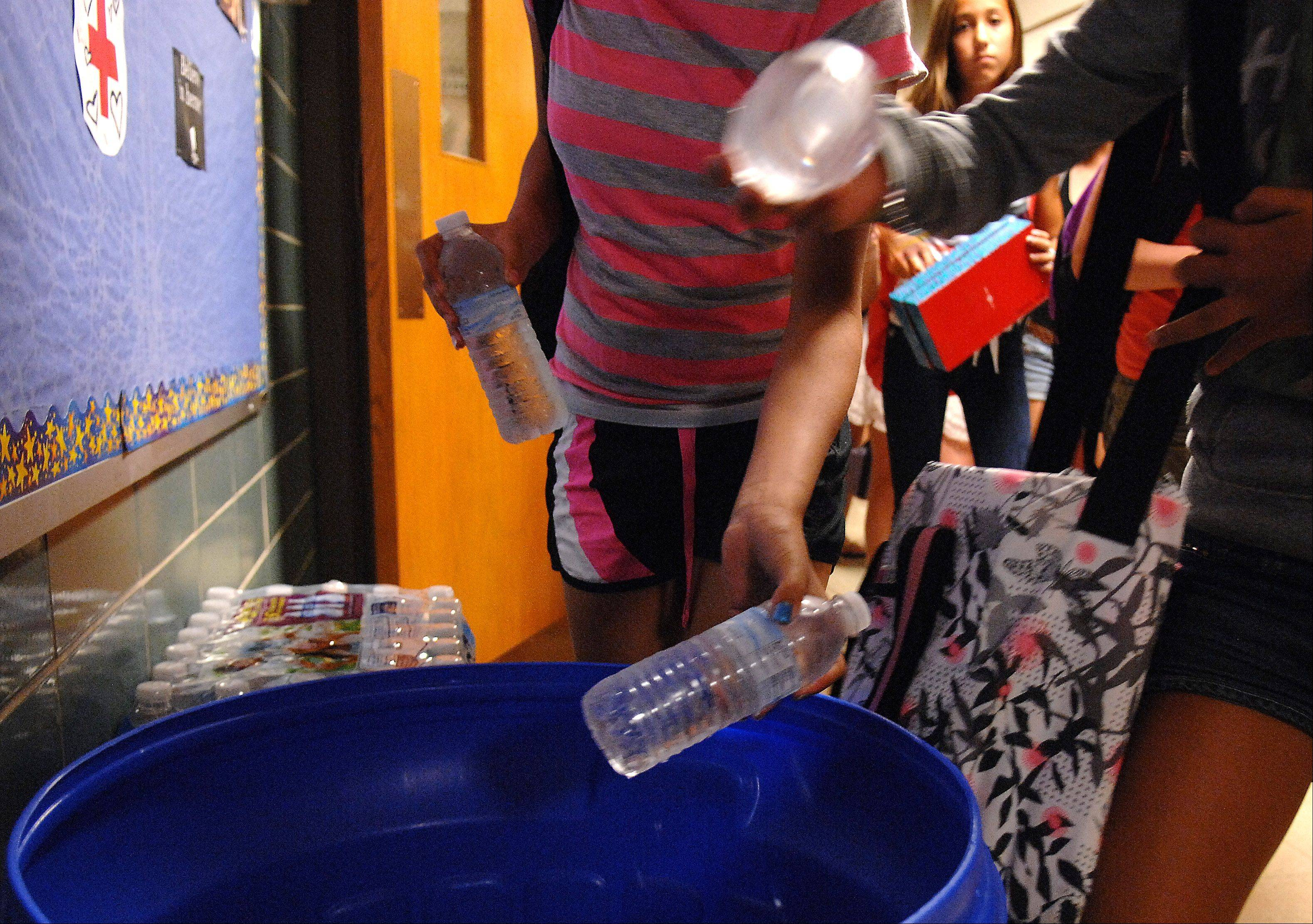 Thompson Middle School students grab bottles of water from icy buckets in the hallway on their way out for an early dismissal Tuesday in St. Charles.