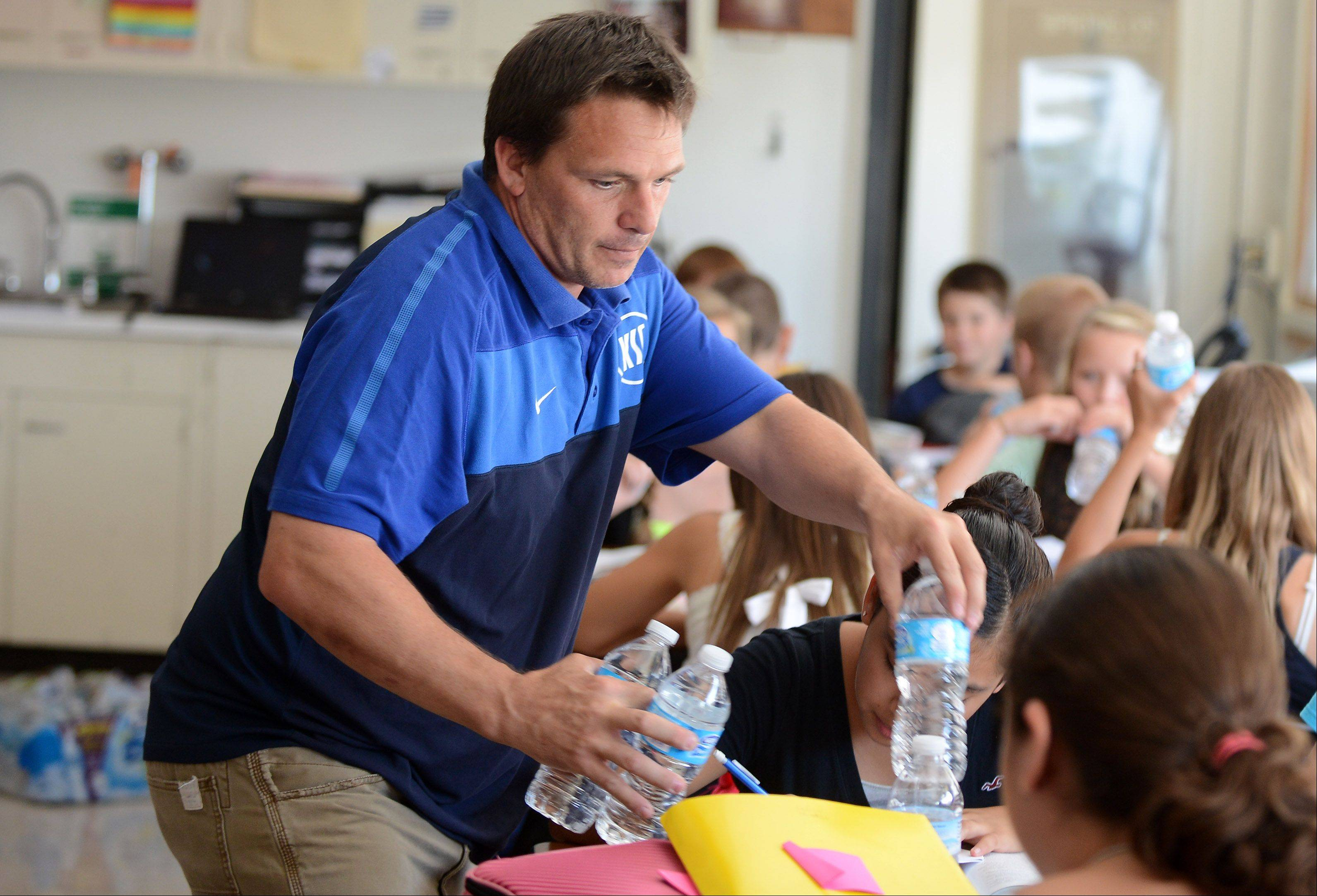 Thompson Middle School social studies teacher Tim Maddie passes out bottle of water to his seventh-grade class while they take a test Tuesday in St. Charles.