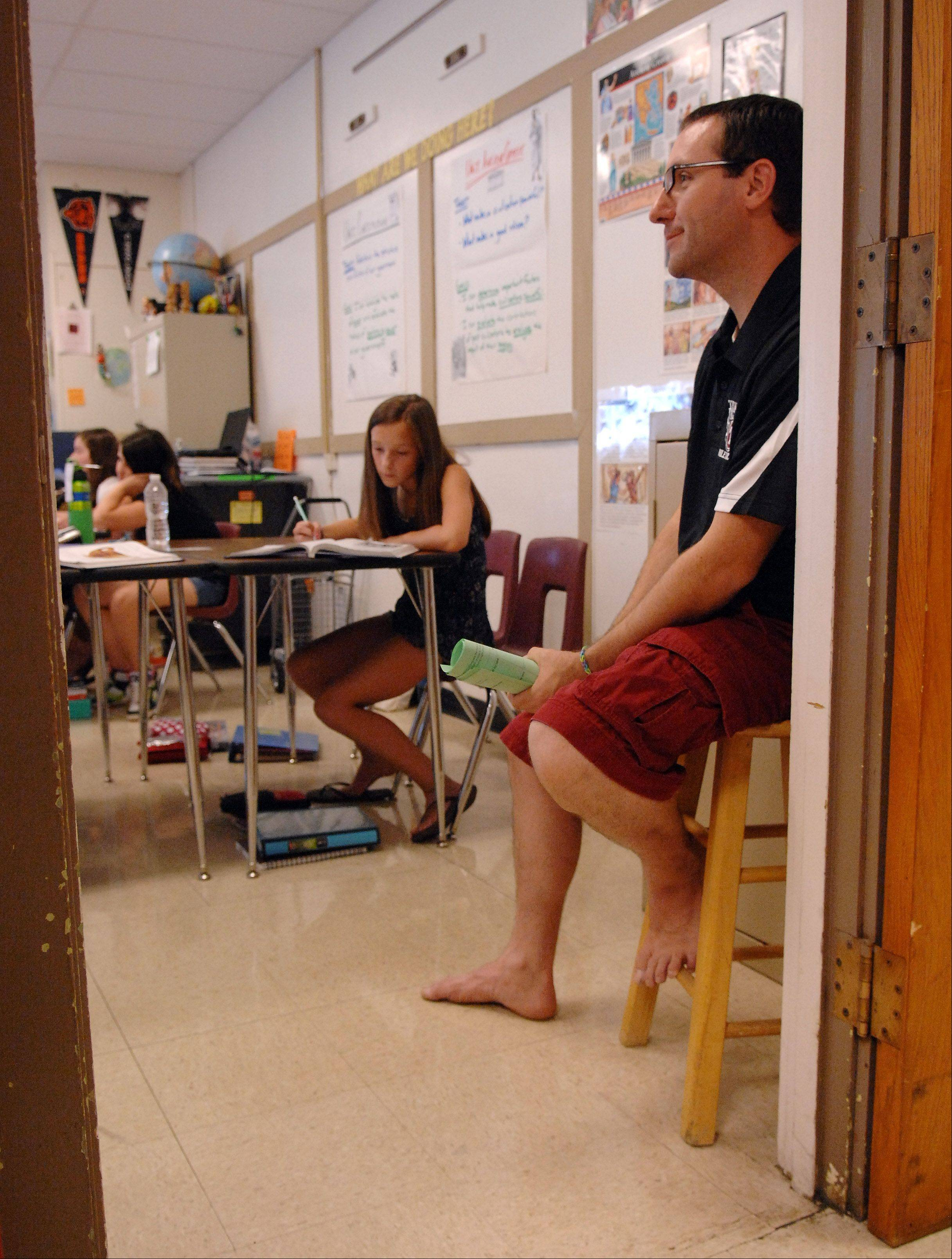 "Thompson Middle School social studies teacher Chris Ashline slipped off his flip-flops and sat by the door as he taught class Tuesday in St. Charles. ""It's the first time in my 10 years of teaching here that I've worn shorts,"" Ashline said."
