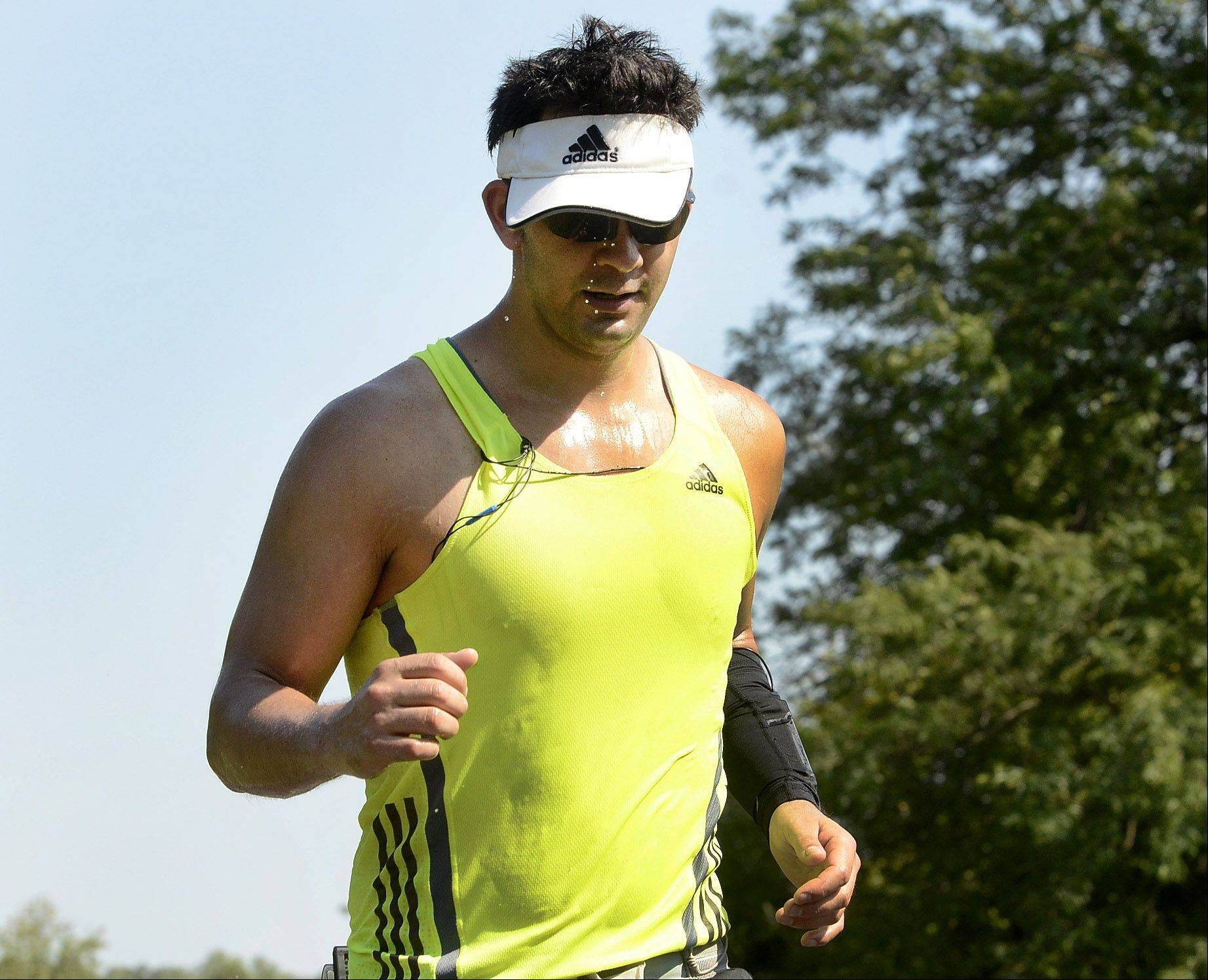 Michael Rosales of Hoffman Estates is training for the Chicago Marathon, and trains regularly along the bike path at Busse West. He runs carrying plenty of water and hydrates constantly in this late summer heat.