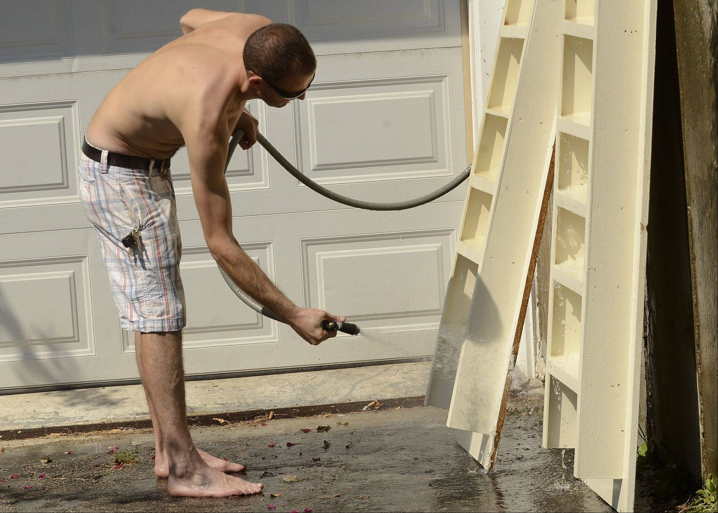 Peter Zob of Hoffman Estates stays cool while hosing down some of his garage shelves. After seeing his kids off to school, he just started this latest task and will go inside as soon as he finishes, not staying out any longer than he has to in this late summer heat.