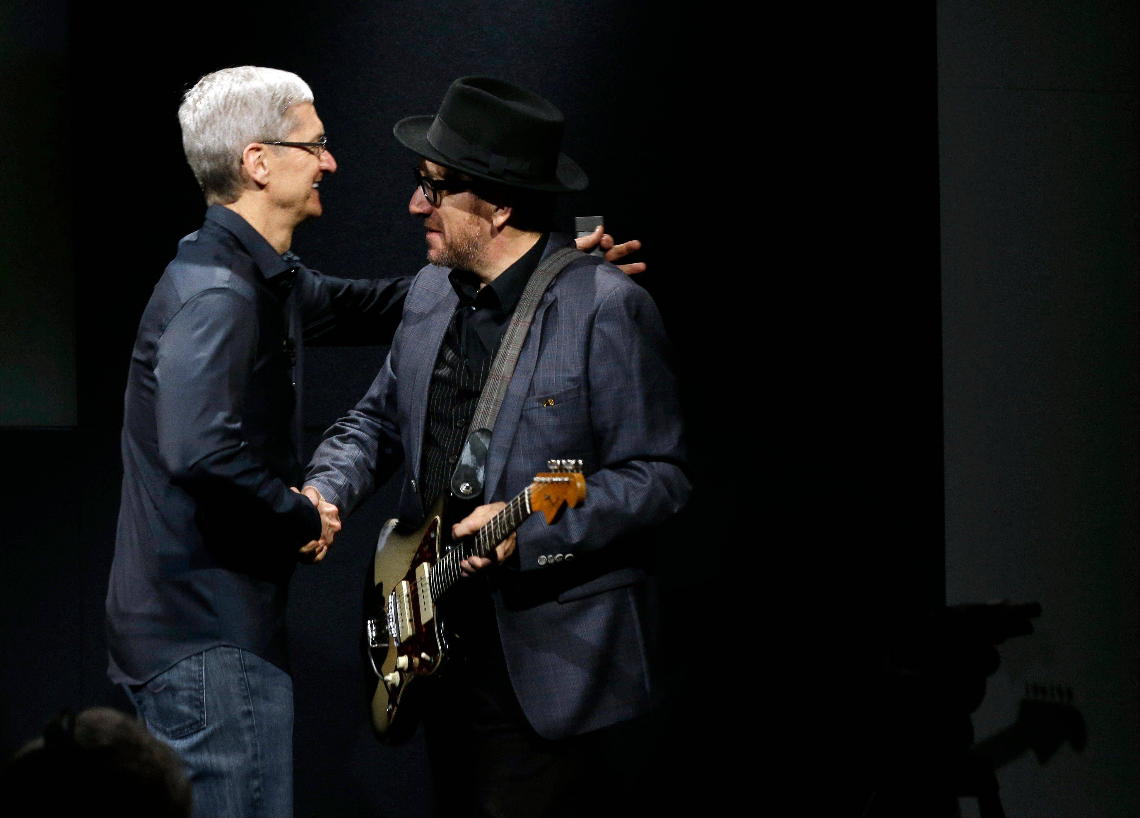 Tim Cook, CEO of Apple, hugs entertainer Elvis Costello, after the new product release in Cupertino, Calif., Tuesday, Sept. 10, 2013. Apple�s latest iPhones will come in a bevy of colors and two distinct designs, one made of plastic and the other that aims to be �the gold standard of smartphones and reads your fingerprint.