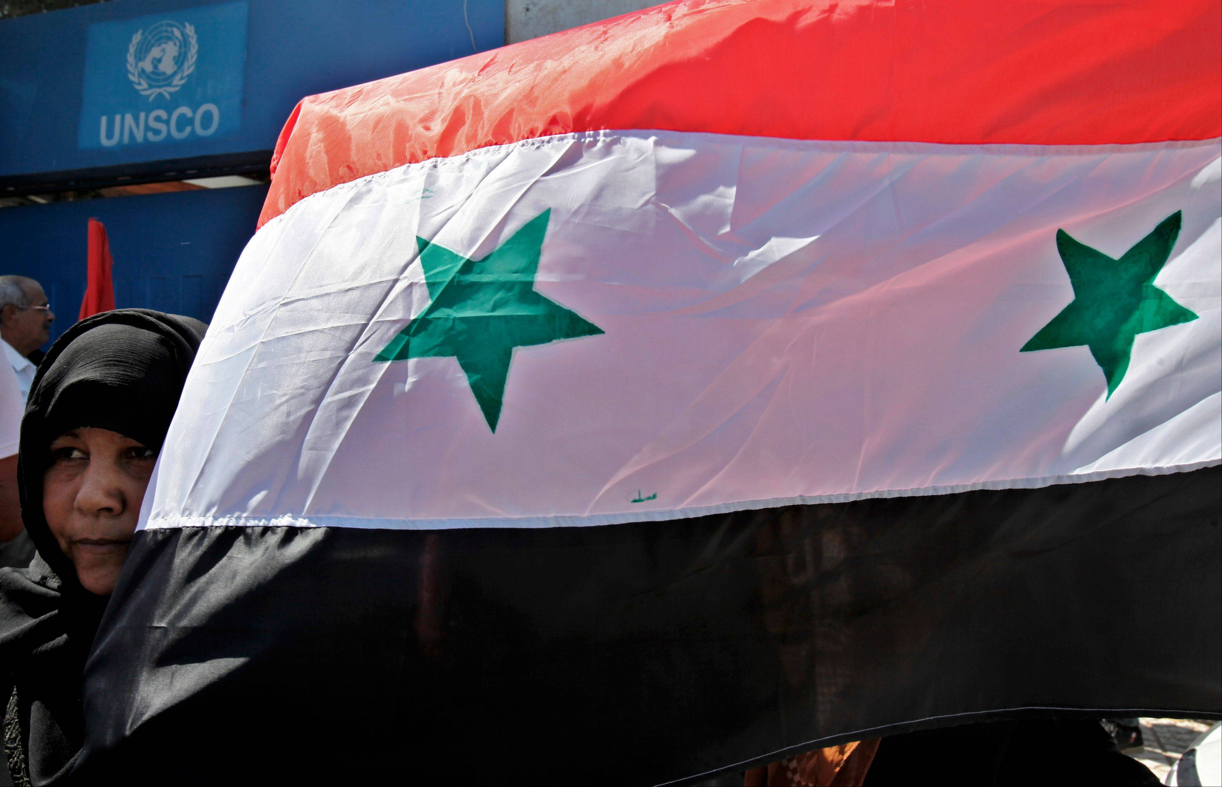 A Palestinian supporter of the Popular Front for the Liberation of Palestine holds a Syrian flag during a protest against a possible military attack by the United States on Syria, in front of the United Nations Special Coordinator for the Middle East Peace Process offices in Gaza City Tuesday.