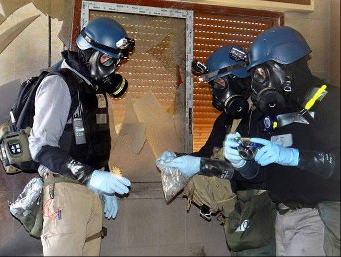 Members of the U.N. investigation team take samples from the ground near Damascus, Syria, on Aug. 29, while gathering evidence of a chemical weapons attack.