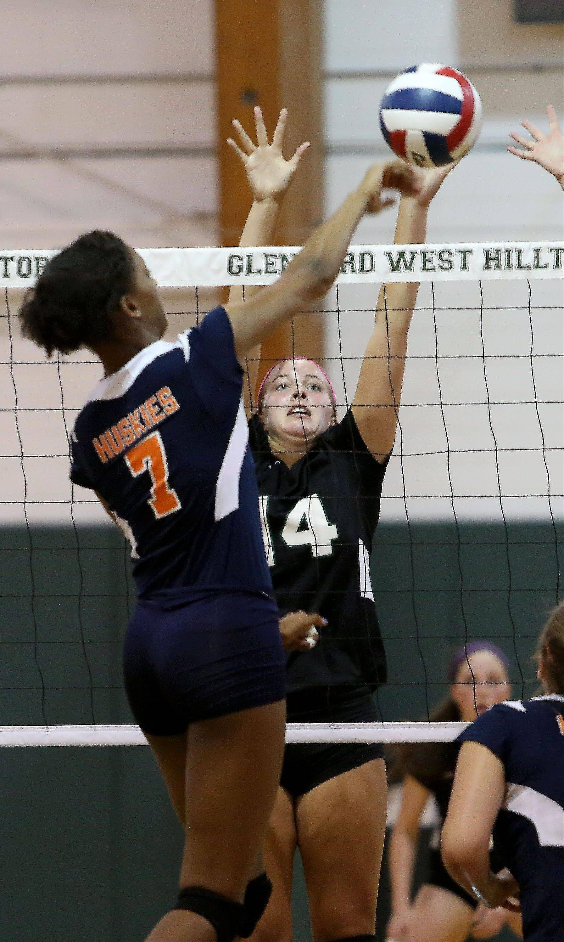 Katie Ball of Glenbard West goes up to block a ball by Symone Speech of Oak Park River Forest during girls volleyball on Tuesday in Glen Ellyn.