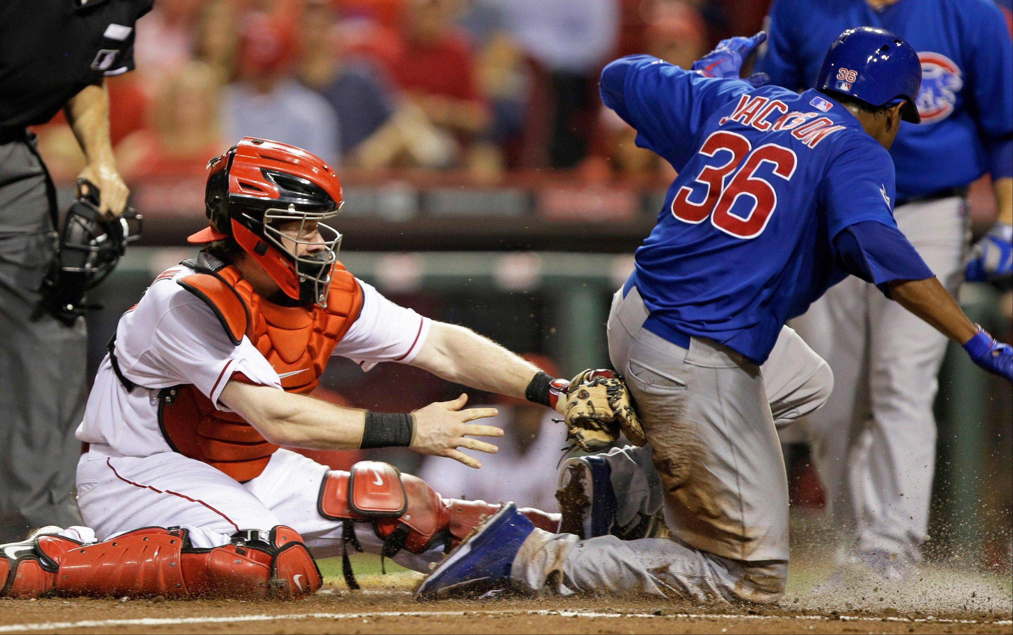 Chicago Cubs' Edwin Jackson (36) is safe at home as Cincinnati Reds catcher Ryan Hanigan is late with the tag in the fourth inning of a baseball game Tuesday in Cincinnati. Jackson scored on a sacrifice fly by Darwin Barney.