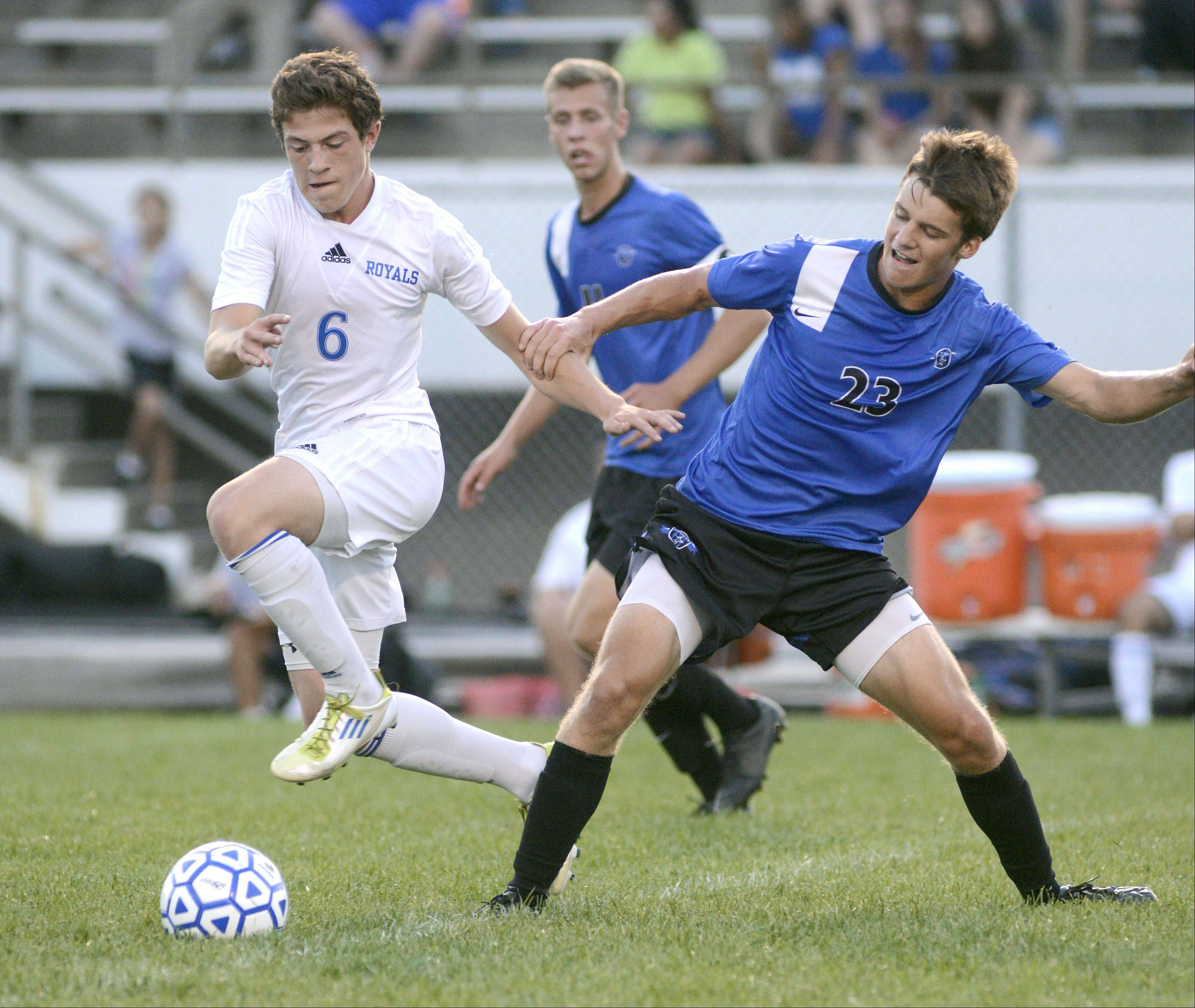 Larkin's Josh Garcia powers through an attempted steal by St. Charles North's Adam Hoffman in the first half on Tuesday at Memorial Field in Elgin.