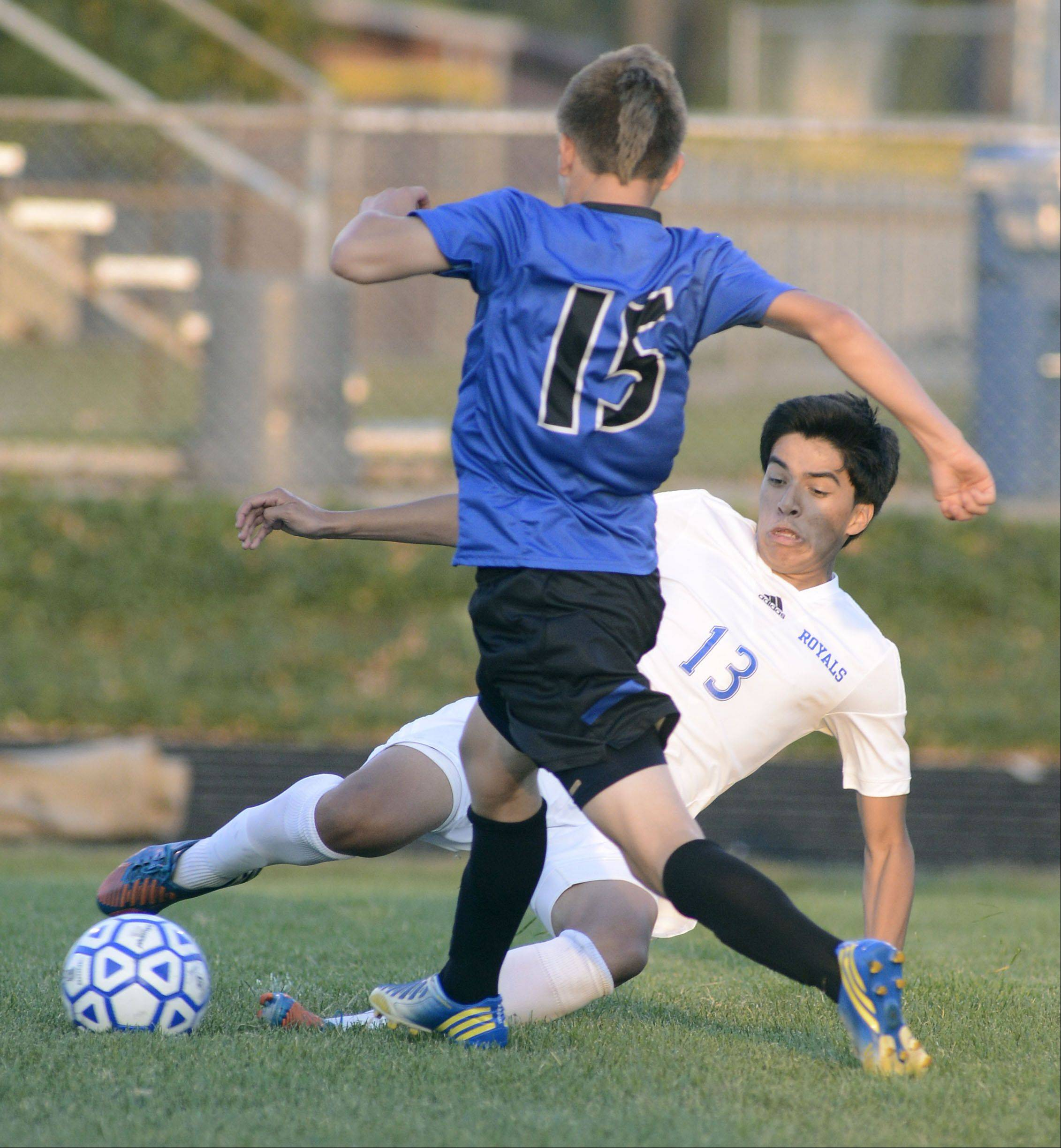 Laura Stoecker/lstoecker@dailyherald.comLarkin's Hector Mendoza slides trying to kick the ball out of the line of St. Charles North's Ryan Olson in the first half on Tuesday at Memorial Field in Elgin.
