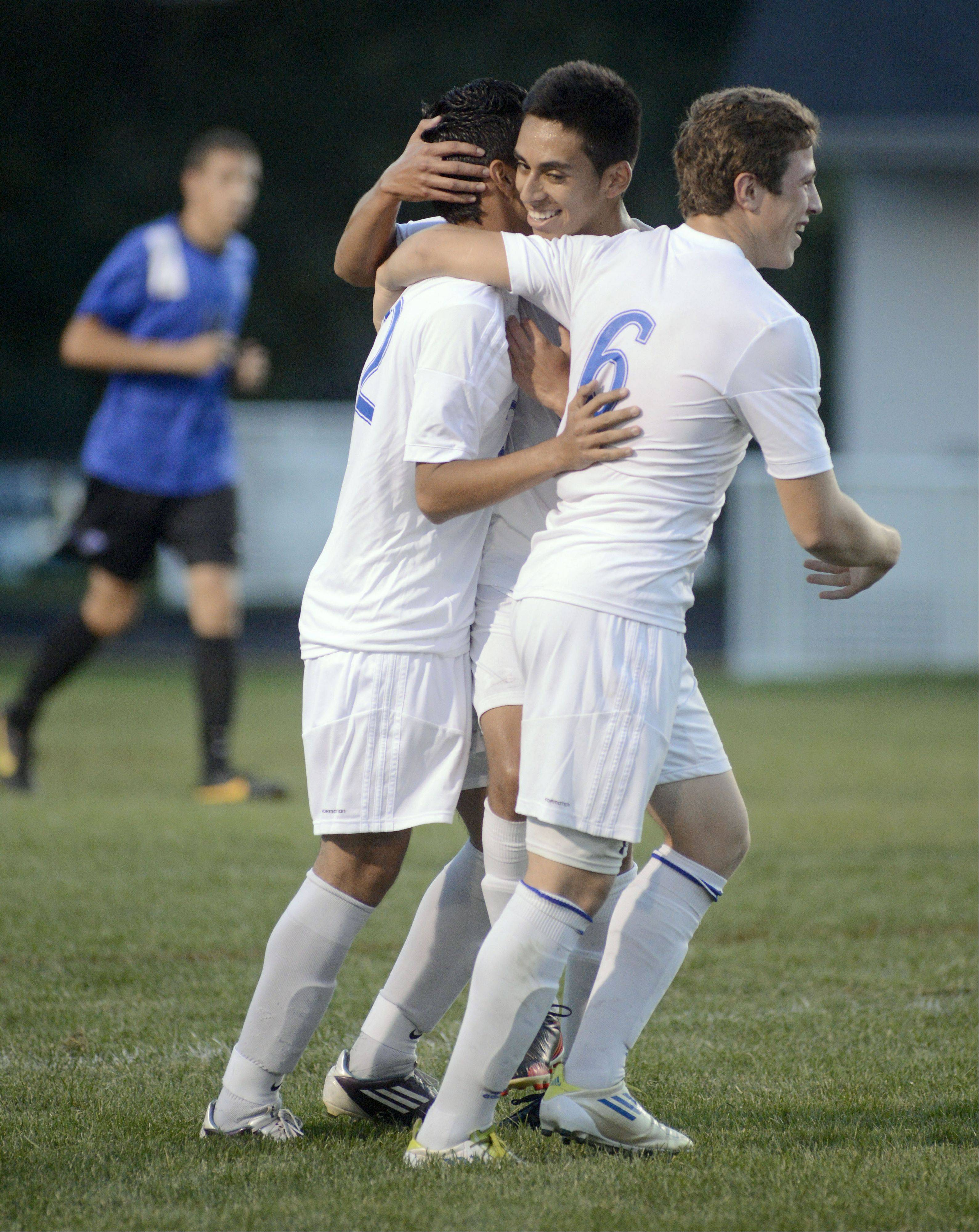 Larkin's Kevin Alas, left, is congratulated by teammates Jesus Avila (facing) and Josh Garcia (6) after scoring the second goal for the Royals in the first half on Tuesday at Memorial Field in Elgin.