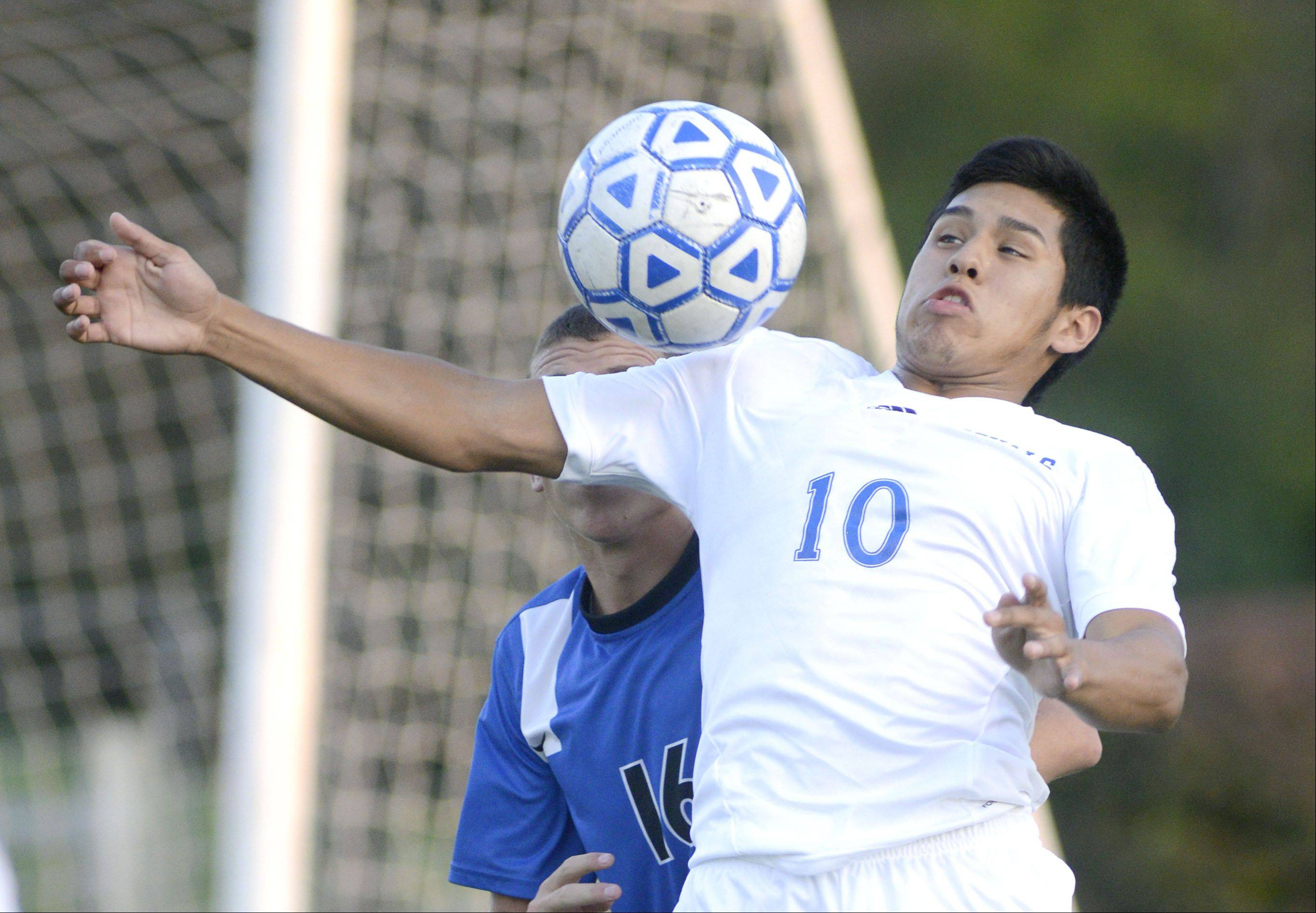 Larkin's Gonsalo Garcia leaps in front of St. Charles North's Nick Graham to deflect the ball with his chest in the first half on Tuesday at Memorial Field in Elgin.