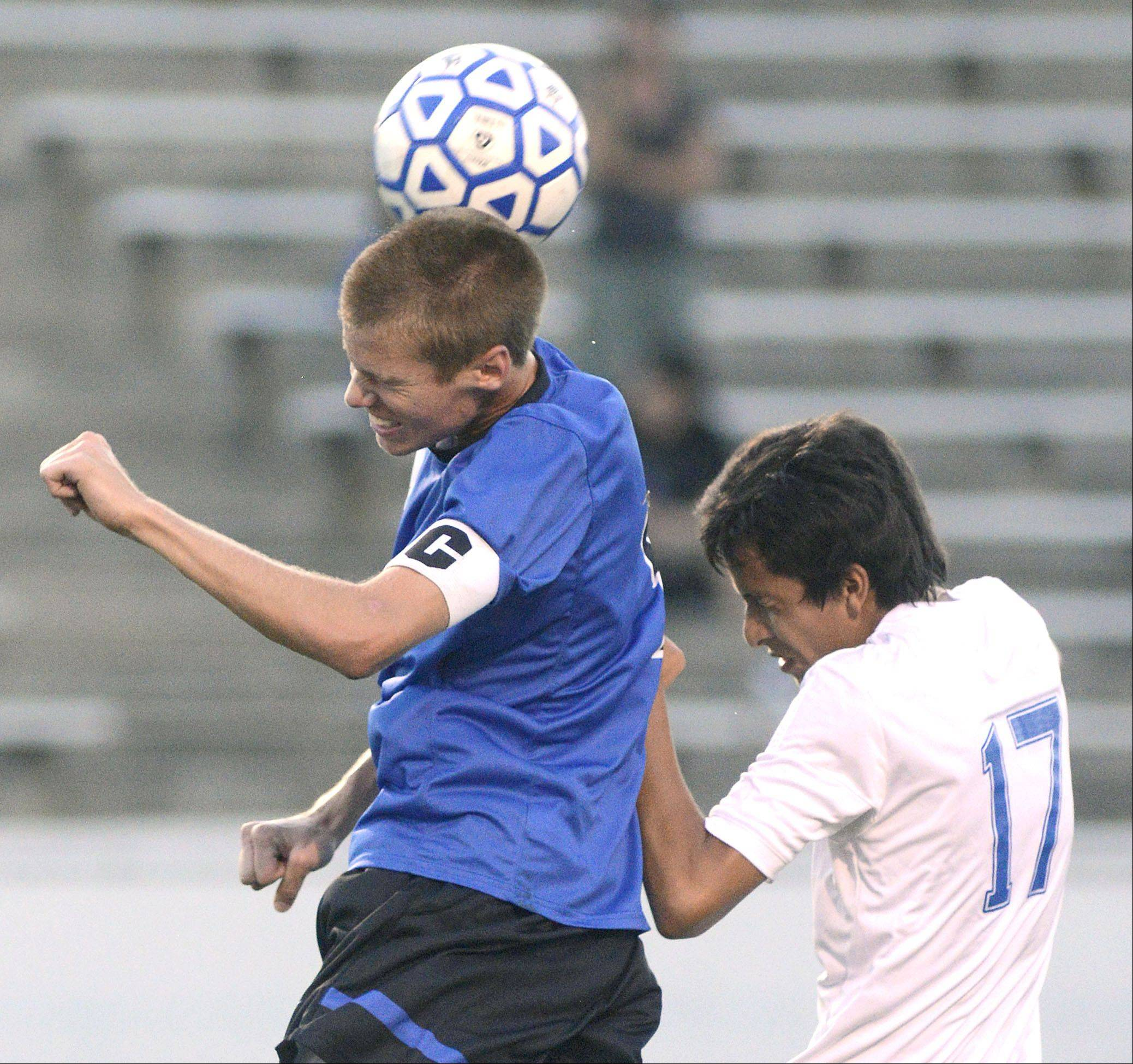 St. Charles North's Brad Johnson beats Larkin's Freddy Jungo to the ball, redirecting it, in the first half on Tuesday at Memorial Field in Elgin.