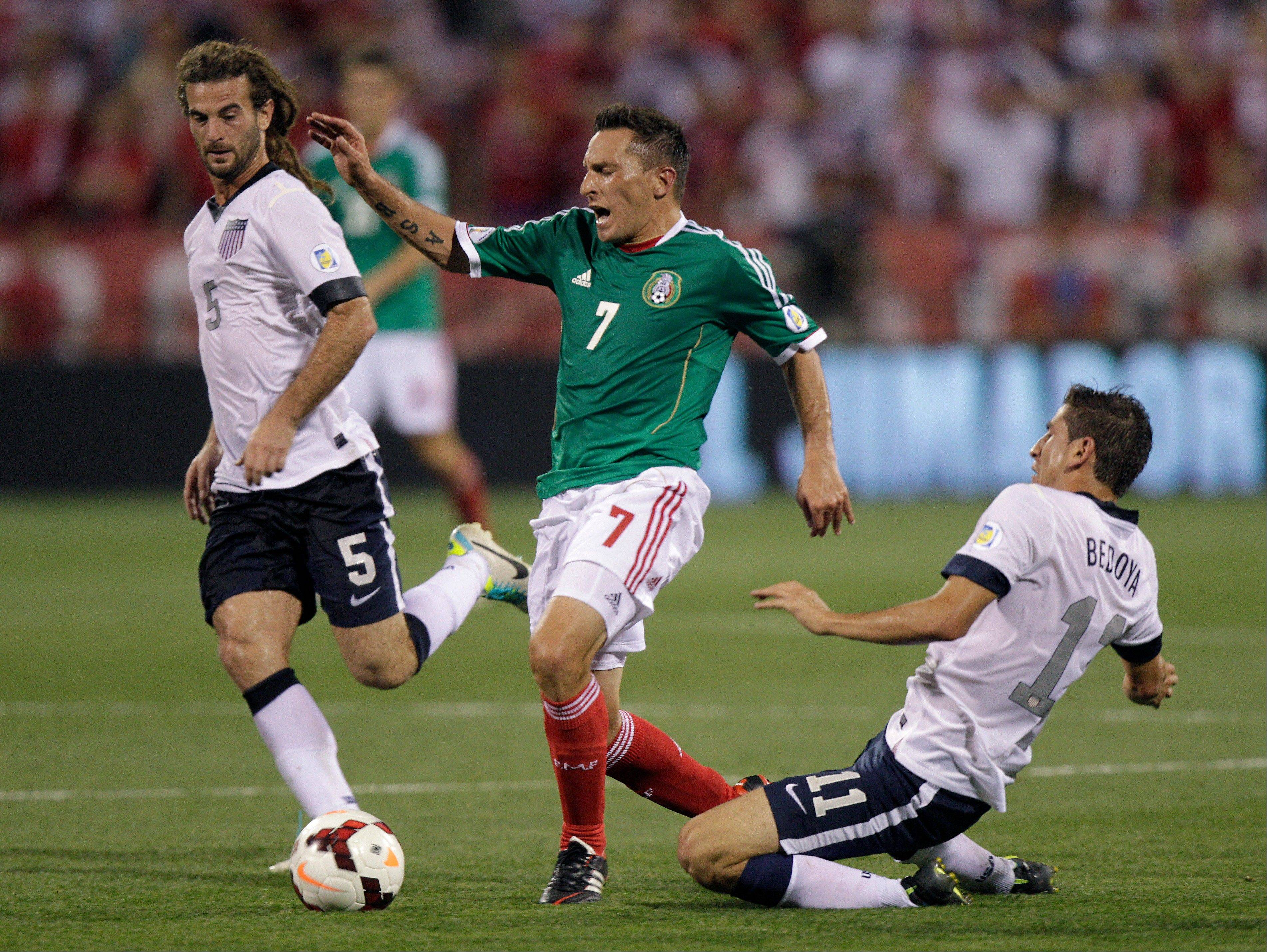 Mexico's Christian Gimenez, center, is tripped by the United States' Alejandro Bedoya, right, as Kyle Beckerman helps to defend during the first half of a World Cup qualifying soccer match Tuesday in Columbus, Ohio.