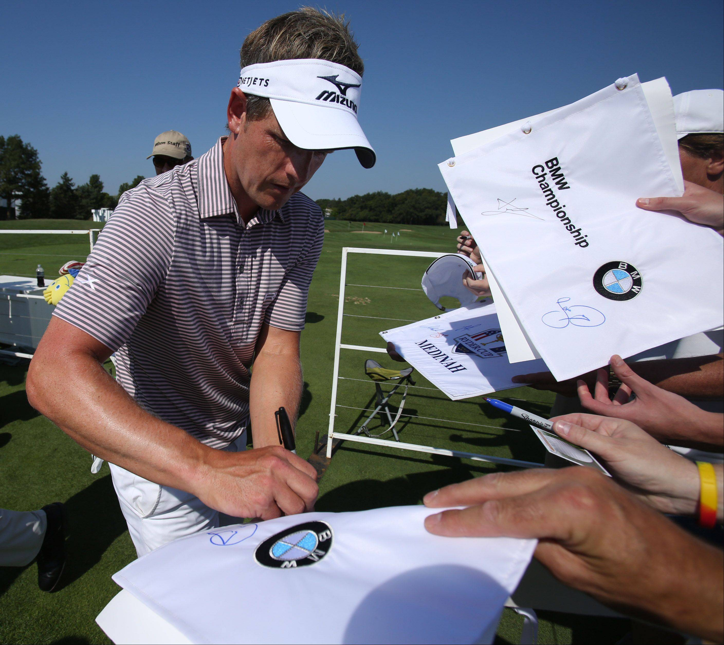Luke Donald signs autographs after practicing on the putting green for the BMW Championship at Conway Farms Golf Club in Lake Forest on Tuesday. Luke's home club is Conway Farms Golf Club.