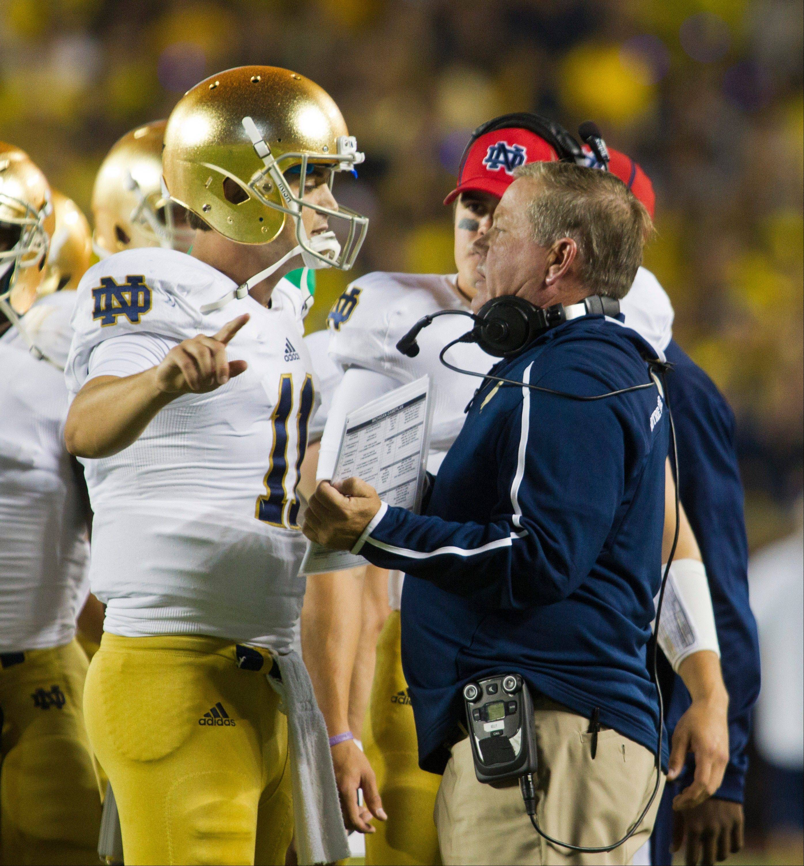 Notre Dame quarterback Tommy Rees talks with head coach Brian Kelly on the sideline during Saturday's game in Ann Arbor, Mich. The Irish threw 12 times in the 13 plays they had in the red zone during the loss to the Wolverines.