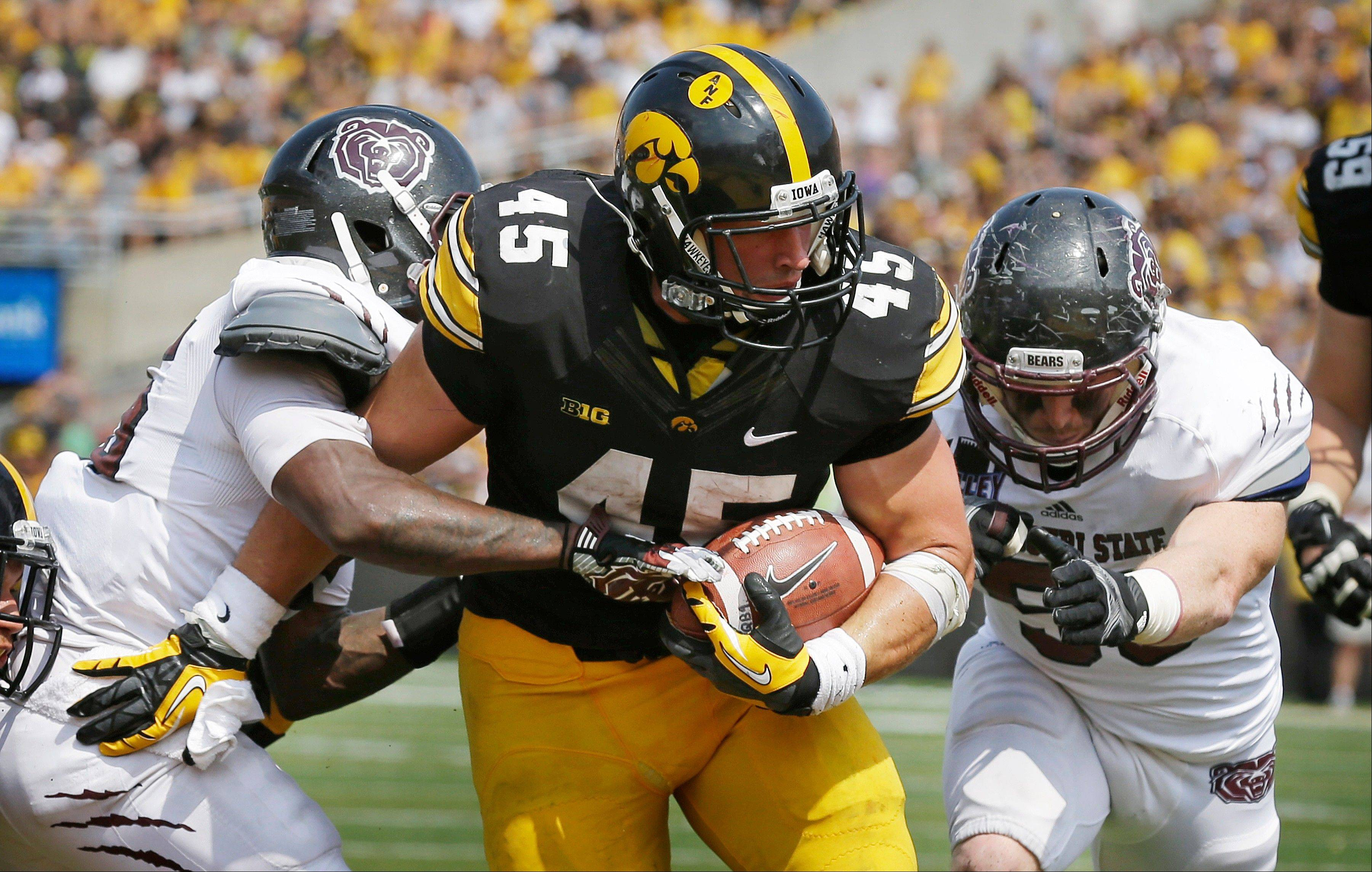 Iowa fullback Mark Weisman, center, scores on a 10-yard run between Missouri State's Sybhrian Berry, left, and Andrew Beisel during the second half of Saturday's game in Iowa City, Iowa.