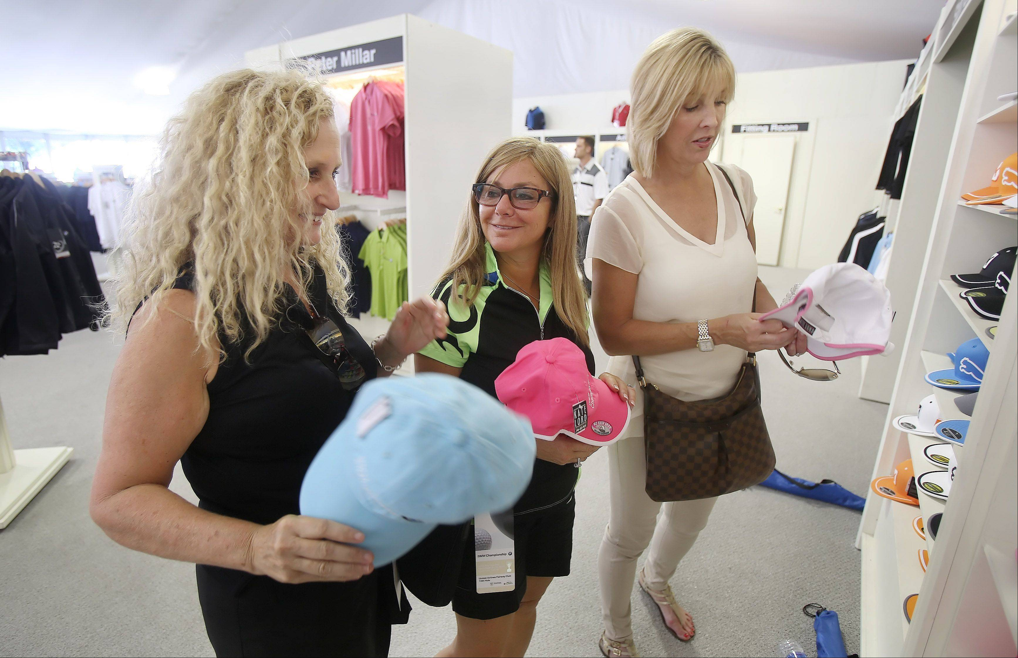 Buffalo Grove residents Sari Wiaz, left, Pam Kahn, and Diana Soskin look at caps in the golf store Monday.