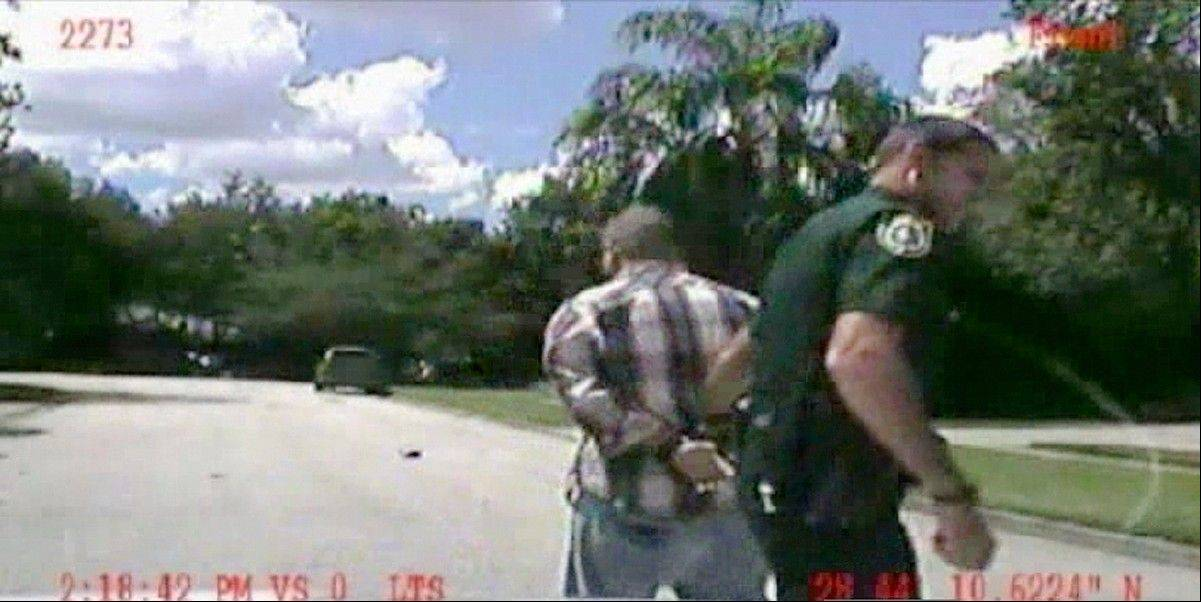 In this still image made from dash-cam video provided by the Lake Mary (Fla.) Police, George Zimmerman is detained by officers on Monday, Sept. 9, 2013. Police in central Florida have been focusing on a broken iPad in their investigation of a domestic dispute between George Zimmerman and his estranged wife Shellie this week. Shellie Zimmerman called 911, saying her estranged husband was in his truck and threatening her and her father with a gun. She also said her husband punched her father in the nose. Hours later, she told police she hadn't seen a gun.