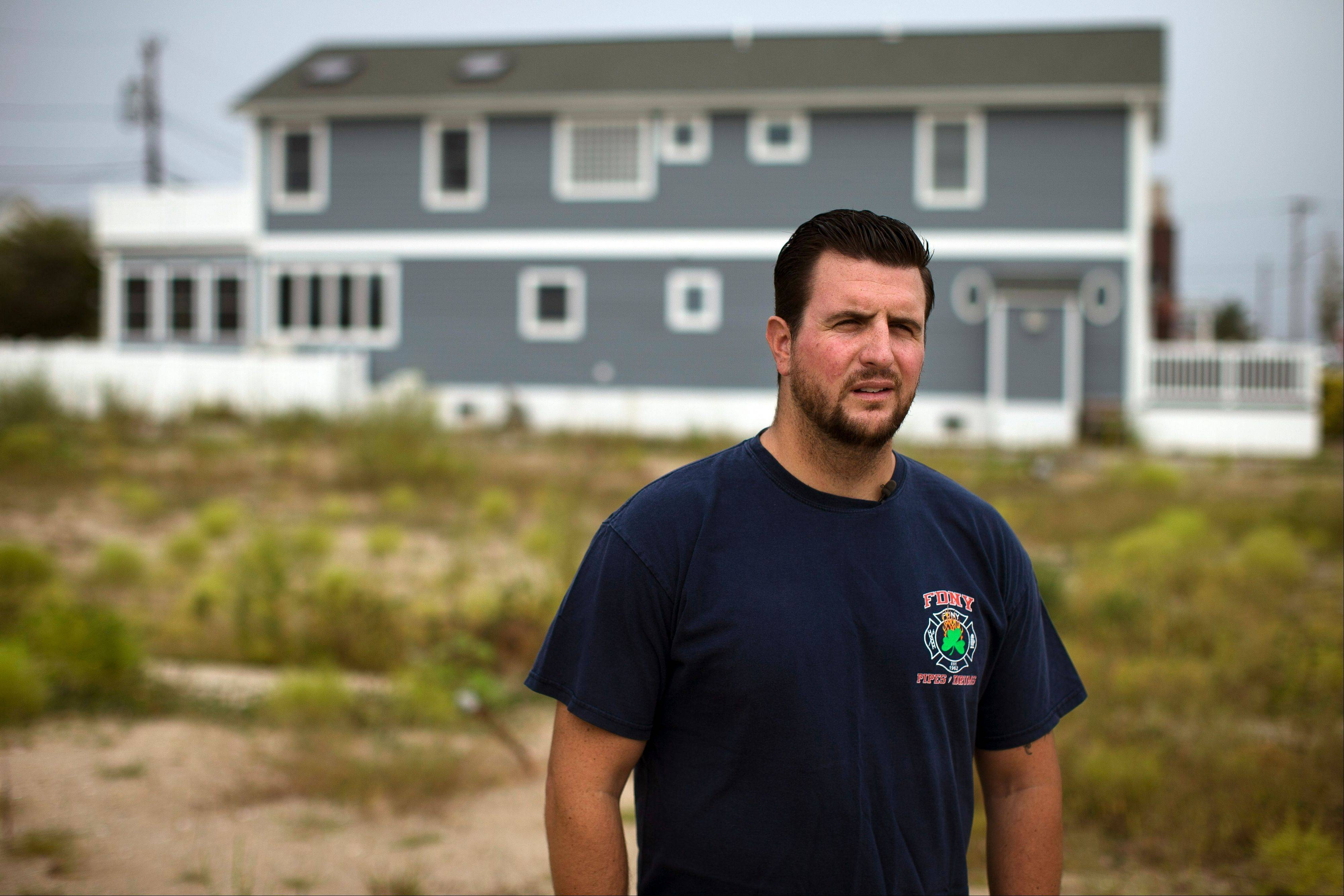 Patrick Dowdell speaks to a reporter in the empty lots where his neighbors houses once stood before they were washed away by Superstorm Sandy, in the Breezy Point neighborhood of New York�s Queens borough. His home, seen behind him, was flooded during the storm, destroying treasured photographs of his firefighter father who perished in the attacks of Sept. 11.
