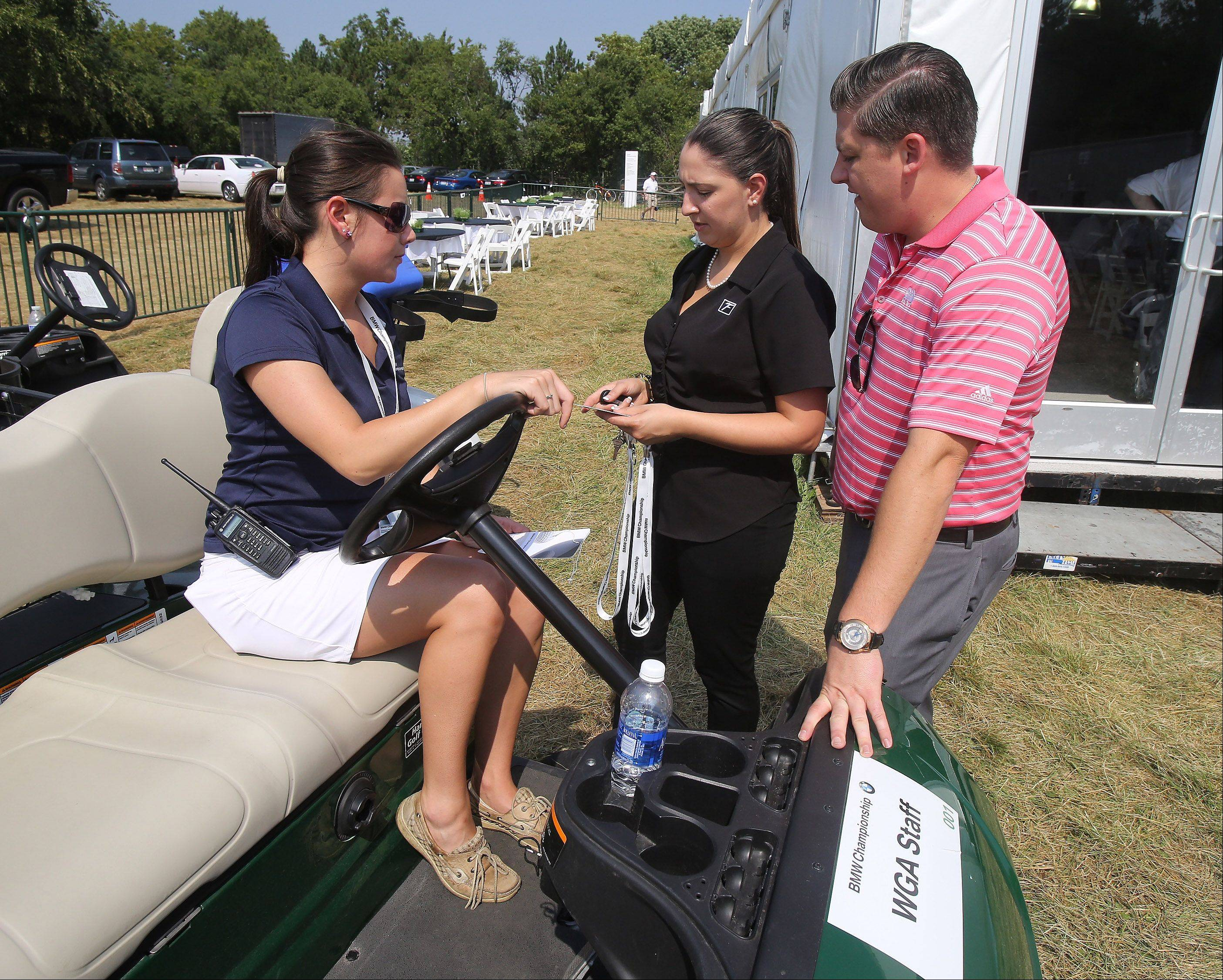 Volunteer Coordinator Kelsey Knapp, left, speaks with vendors outside the volunteer hospitality tent at the BMW Championship at Conway Farms Golf Club in Lake Forest. Volunteers are a crucial part of tournament operations, organizers say.