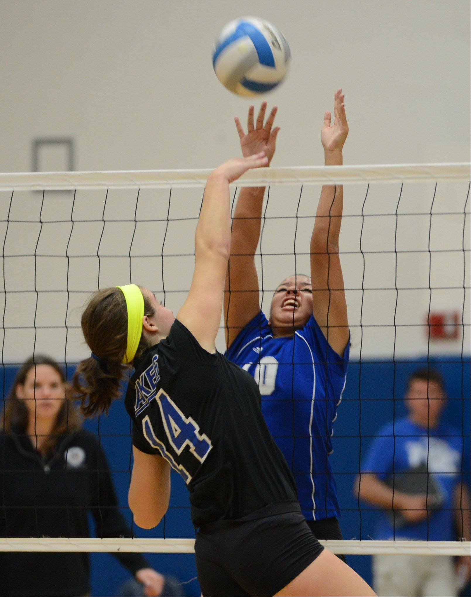 Lakes� Megan Behrendt (14) knocks the ball past Vernon Hills� Tori Smith during Wednesday night�s volleyball game in Vernon Hills.