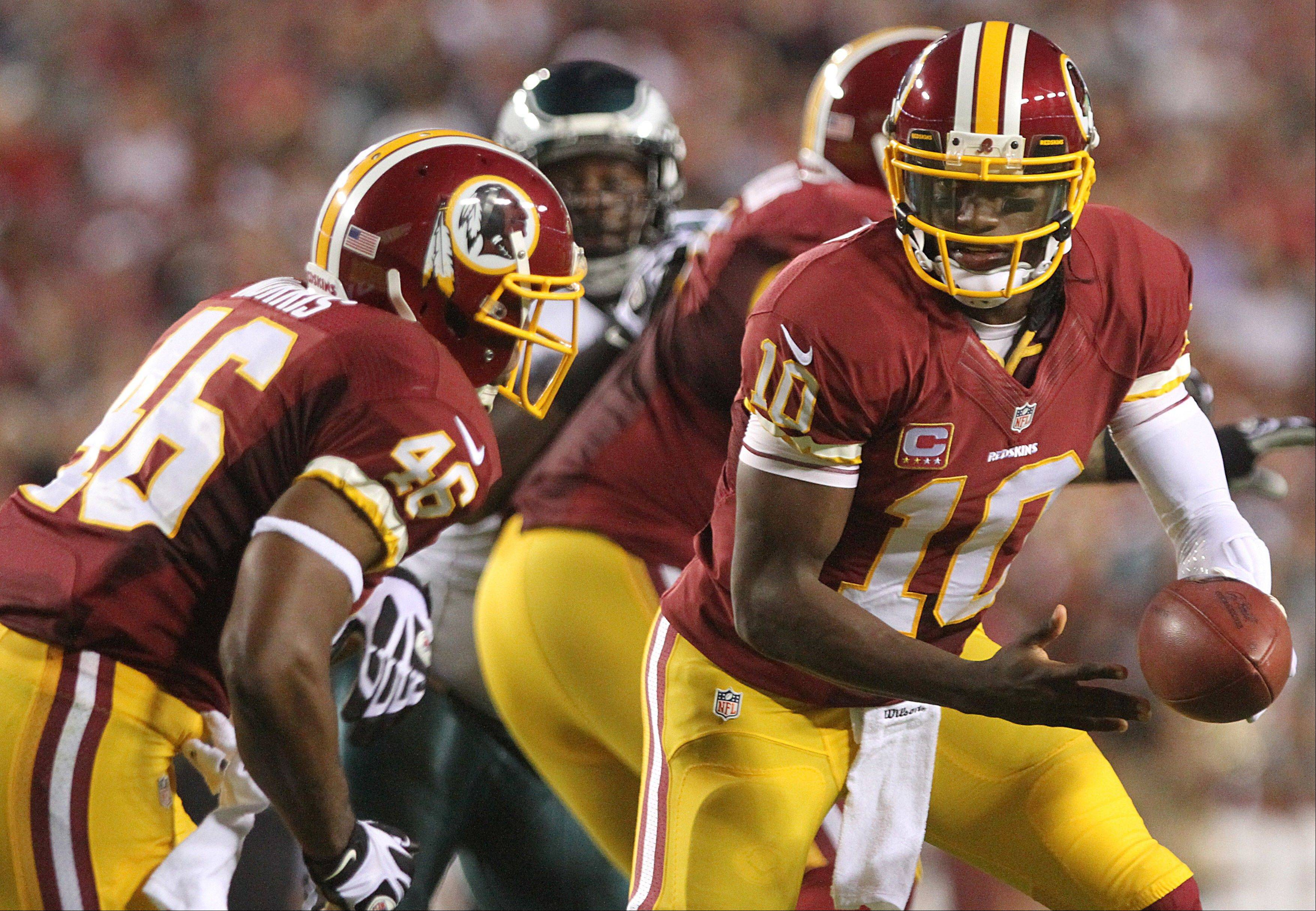 Washington Redskins quarterback Robert Griffin III turns to hand off to running back Alfred Morris during game Monday against the Philadelphia Eagles. Owner Dan Snyder has vowed never to change the team�s name.