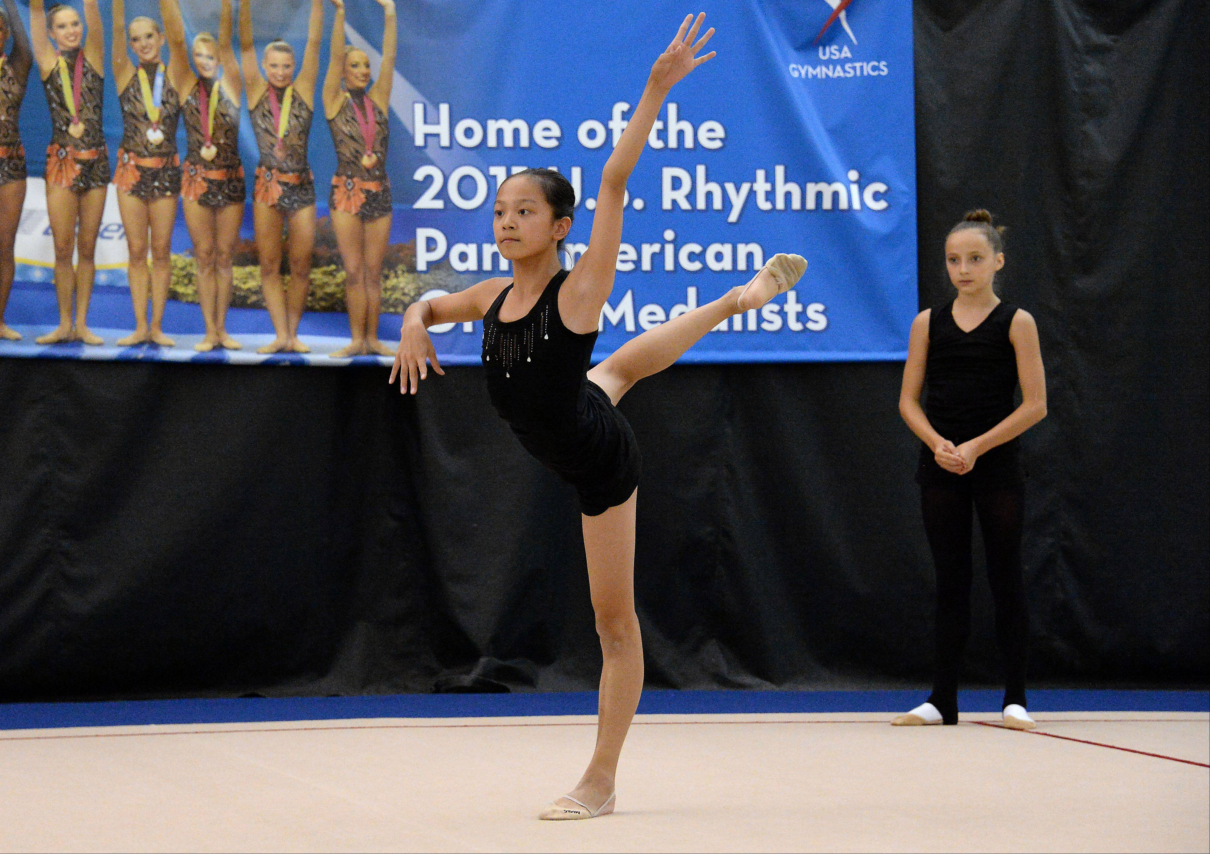 Laura Zeng, 13, of Libertyville practices a routine at the North Shore Rhythmic Gymnastic Center in Deerfield as Camilla Feeley, 13, of Lincolnshire looks on. Both are members of the junior national team and Laura is the reigning national junior champion.
