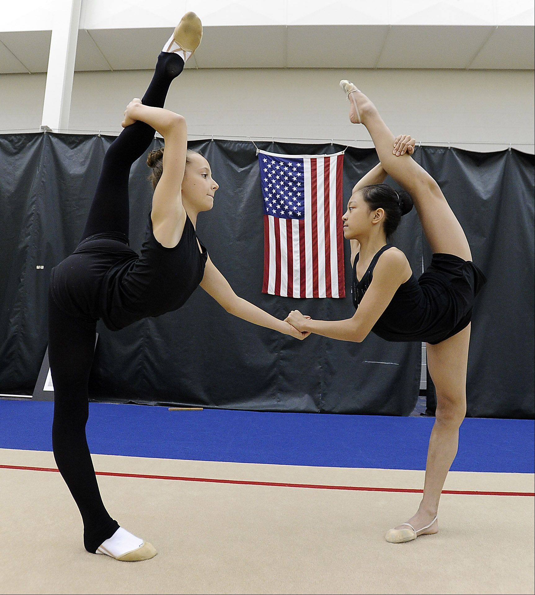 Camilla Feeley, 13, left, of Lincolnshire and Laura Zeng, 13, of Libertyville stretch during a recent training session at the North Shore Rhythmic Gymnastic Center in Deerfield. Both are members of the junior national team and Laura is the reigning junior national champion.