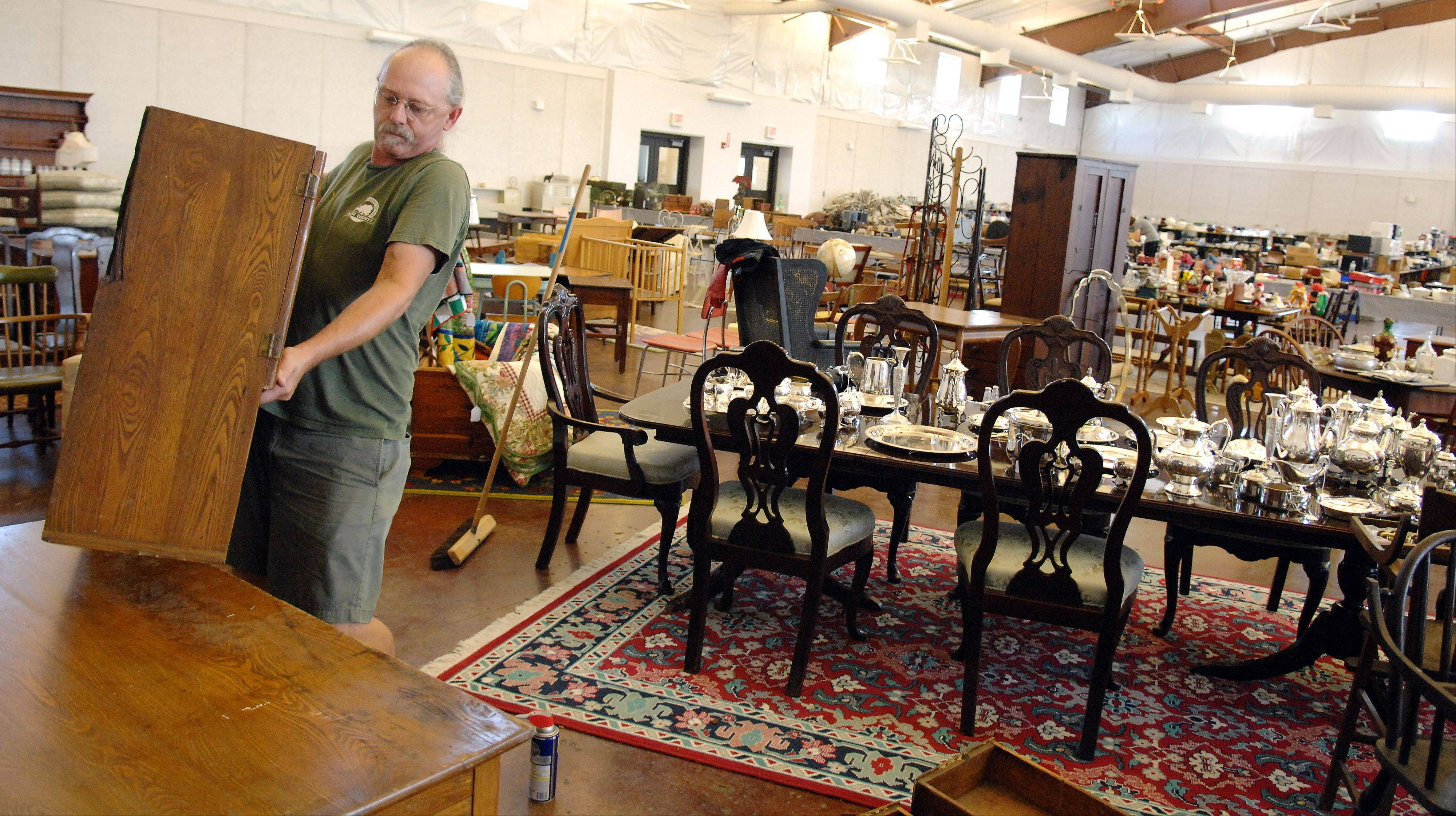 Jeff Ralston places a hutch on top of a desk this week as he helps set up for the St. Peter Barn Sale coming up Saturday and Sunday at the Kane County Fairgrounds in St. Charles.