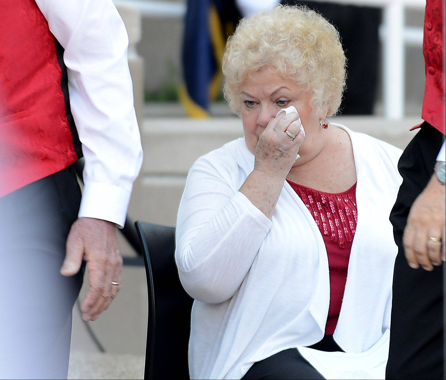 "Sandra Woolcott wipes away a tear before joining the Mood Makers Barbershop Quartet in a rendition of ""Battle Hymn of the Republic"" during the city of Elgin's Sept. 11 ceremony in front of the police department building Wednesday."