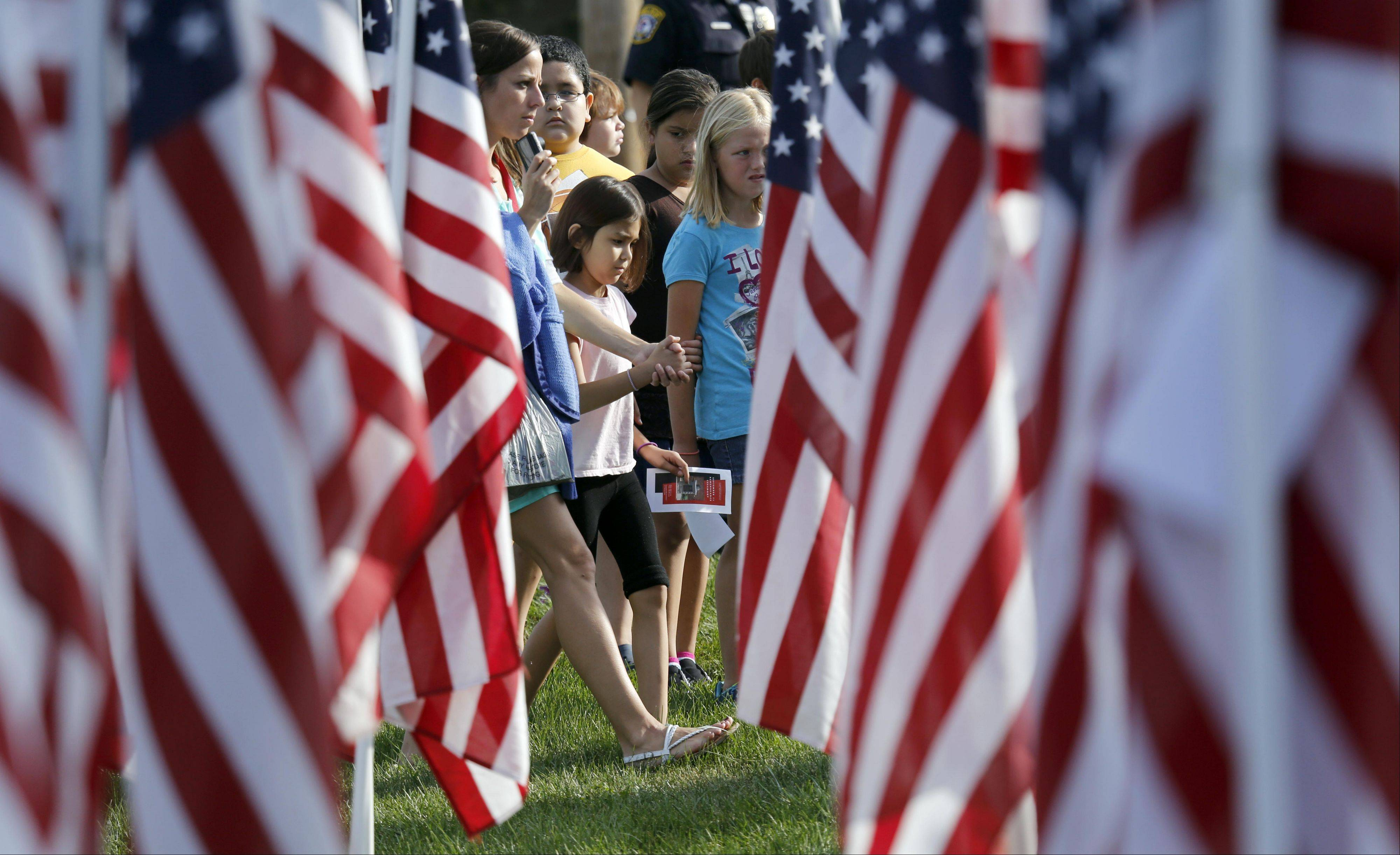 Students from Parkview Elementary School who attended the Sept. 11 ceremony Wednesday at Carpentersville Fire Station 1 file past some of the more than 400 flags representing the firefighters, port authority, and police officers that lost their lives that day.
