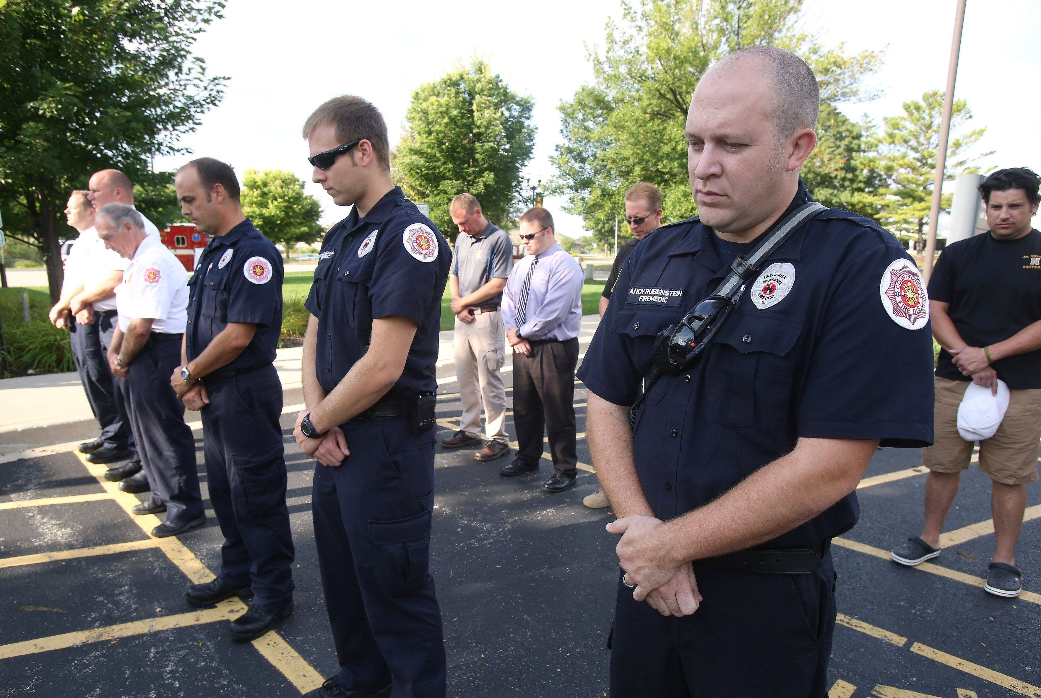 Firefighter/paramedics Andy Rubenstein, right, Chad McCormick and members of the Countryside Fire Protection District and the Vernon Hills Police Department hold a moment of silence in remembrance of Sept. 11 Wednesday at the Deerpath fire station.
