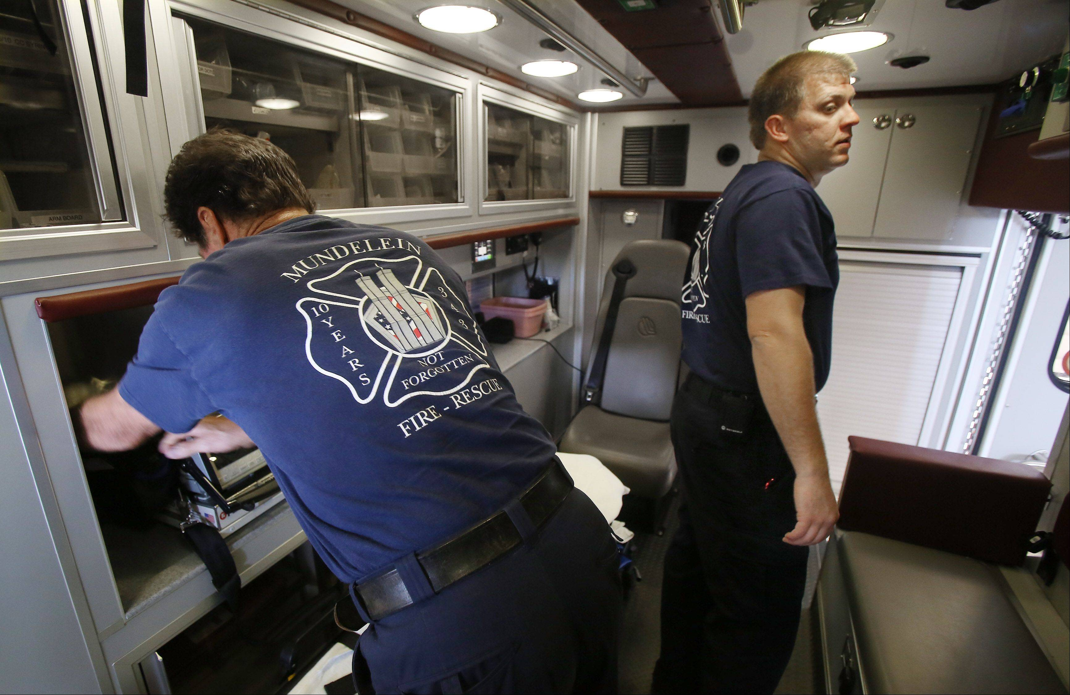 Firefighter/paramedics Ed Anderson, left, and Dan Buhrmester work on the ambulance as firefighters with the Mundelein Fire Department wear FDNY T-shirts in remembrance of Sept. 11 Wednesday at the Midlothian fire station.