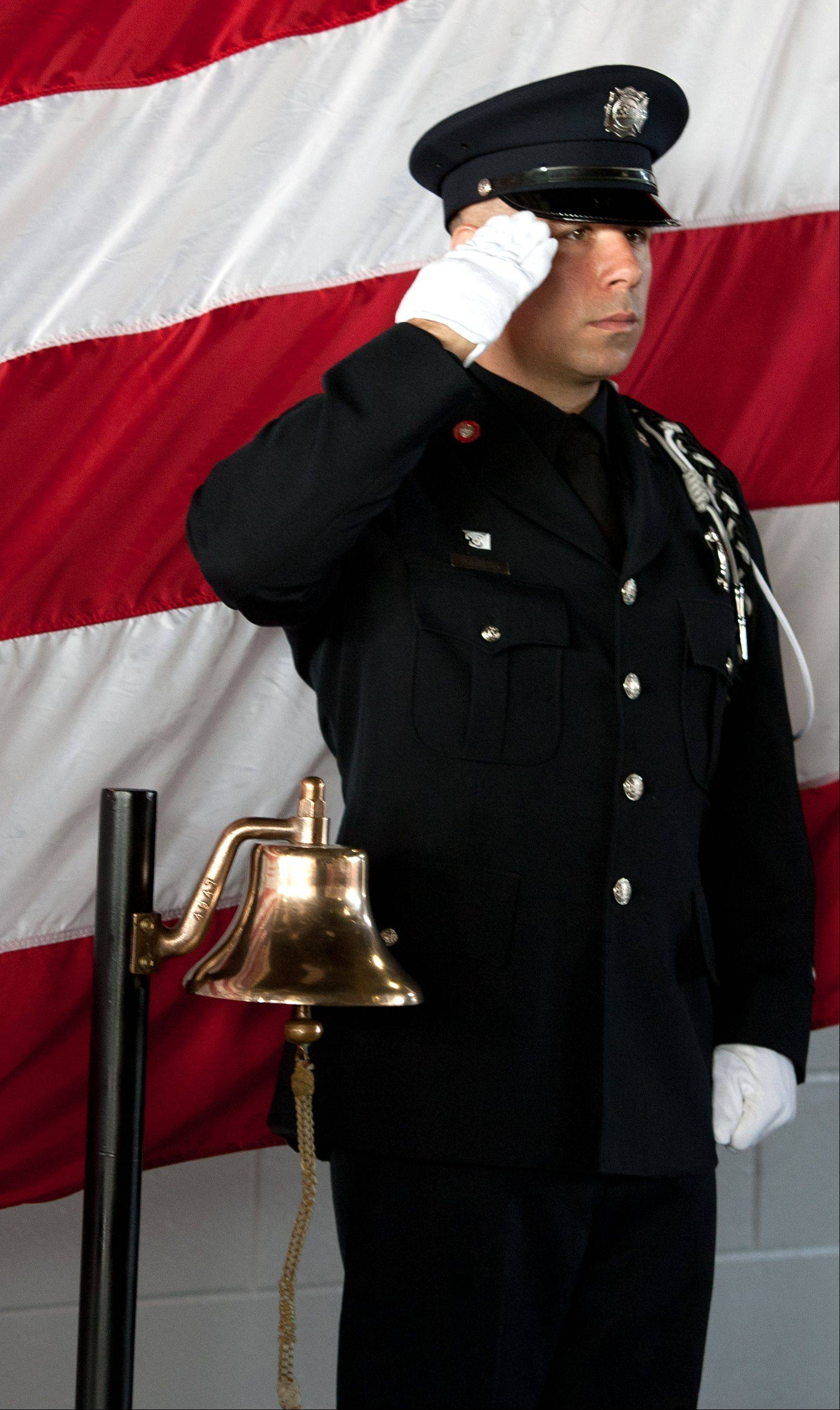 Firefighter Danny Stelter salutes the fallen after ringing a bell to commemorate the north tower collapse, during a Sept. 11 Anniversary Commemoration Ceremony at the Carol Stream Fire Protection District Headquarters.