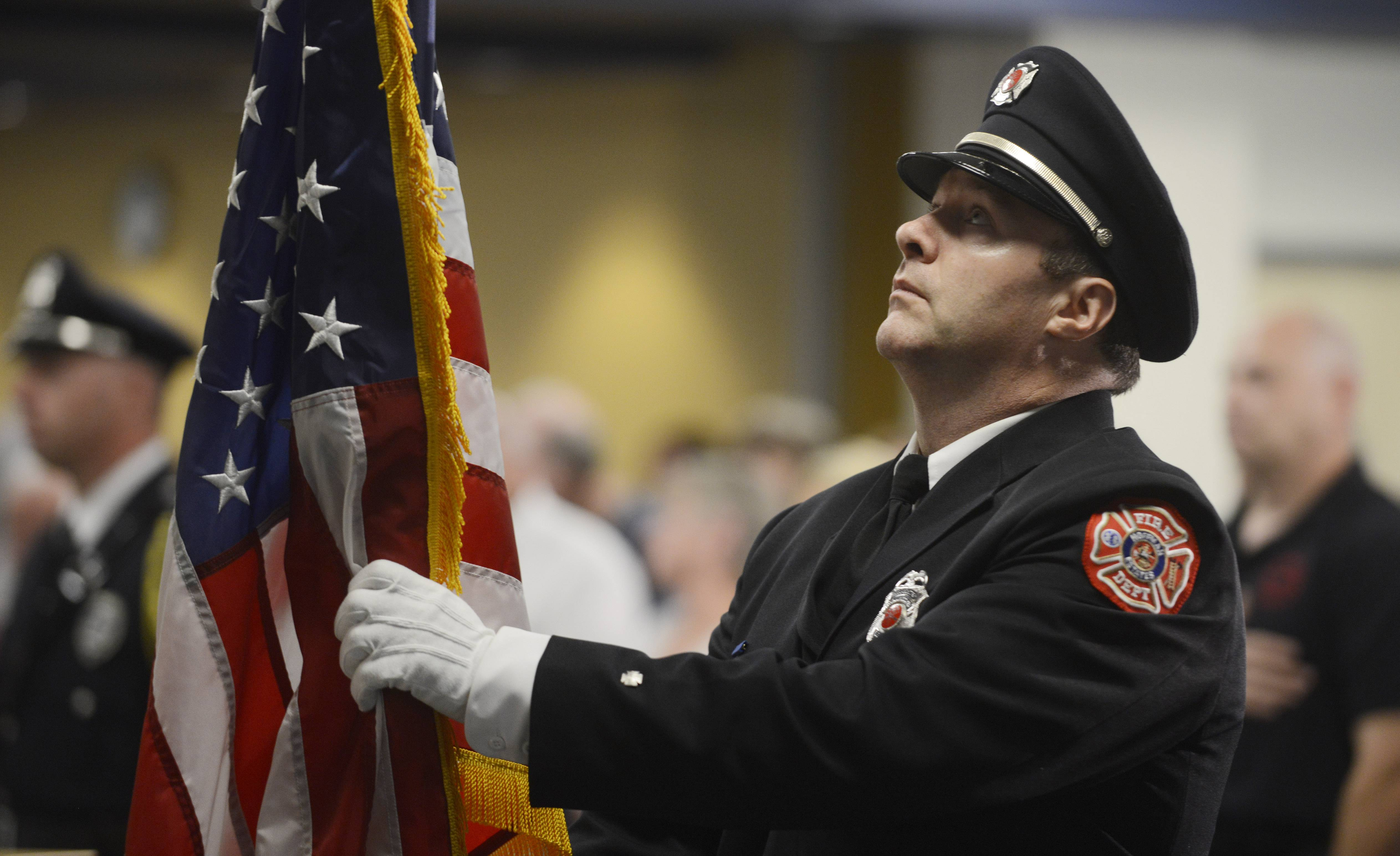Hoffman Estates Firefighter/paramedic and honor guard member Rob Petz places the colors during the Village of Hoffman Estates' memorial service for victims of the September 11, 2001 terrorist attacks, held Wednesday evening at the village hall.