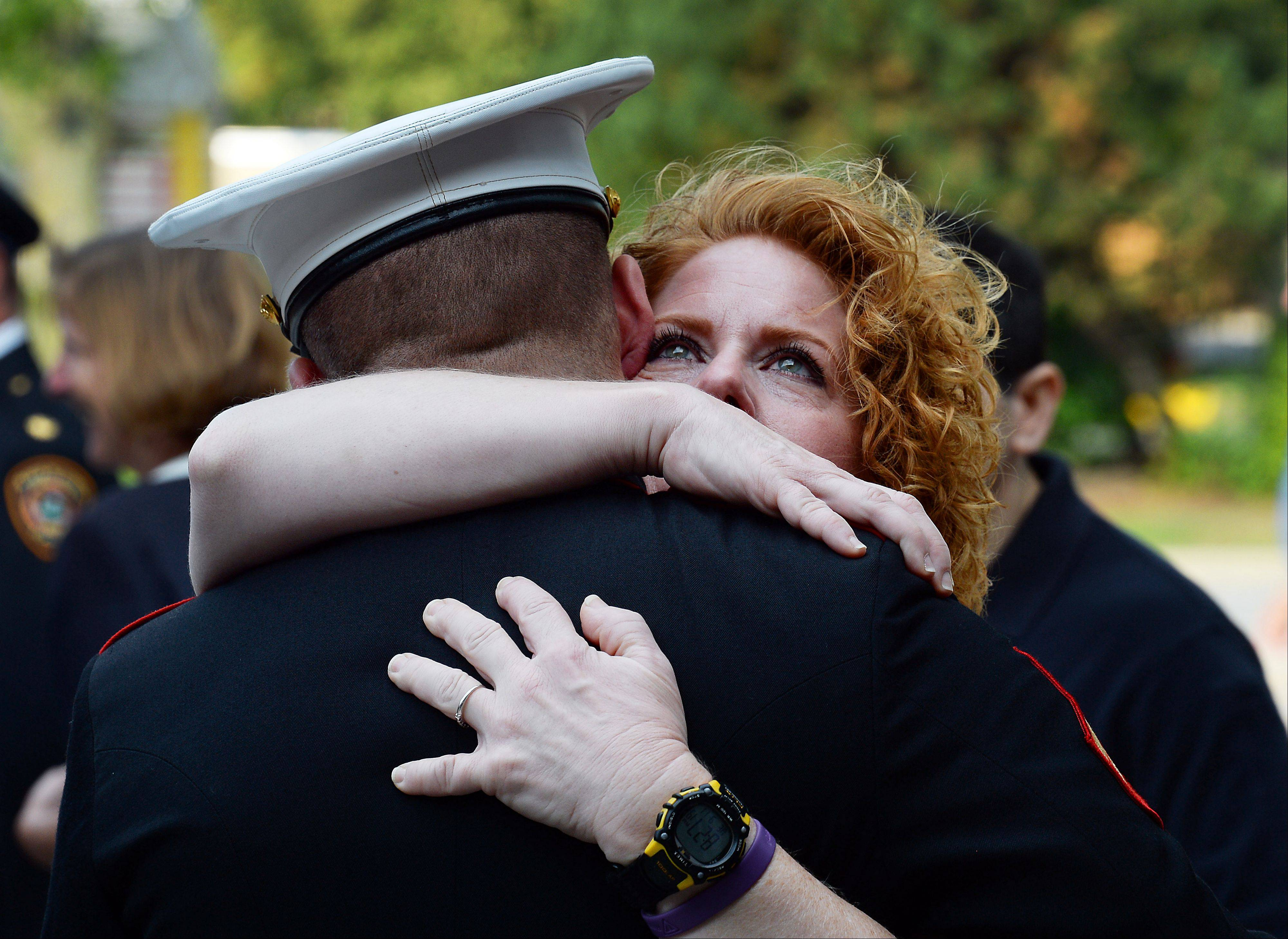 The trumpet of Marine Marshal Macri of Hoffman Estates played Taps and in return his mom Stacey gives him a hug as they honored the fallen at the Sept. 11 memorial and Patriot Day ceremony at fire station 1 on Wednesday.