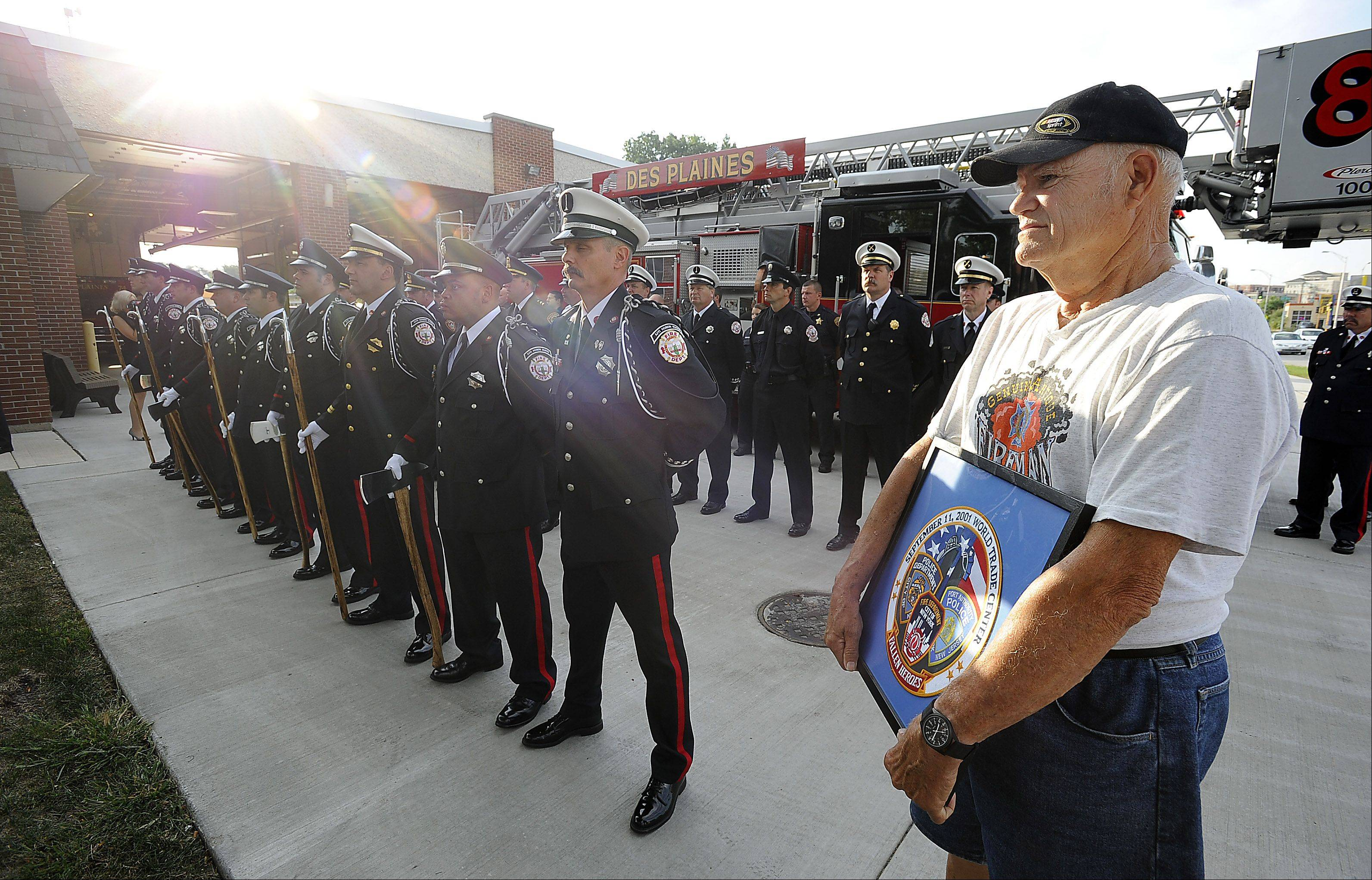 "Ken Koeppen, Mt. Prospect Fire Department holds a remembrance plaque at the Des Plaines Fire Department as they honor the fallen at the Sept. 11 memorial and ""Patriot Day"" ceremony at fire station 1 on Wednesday."