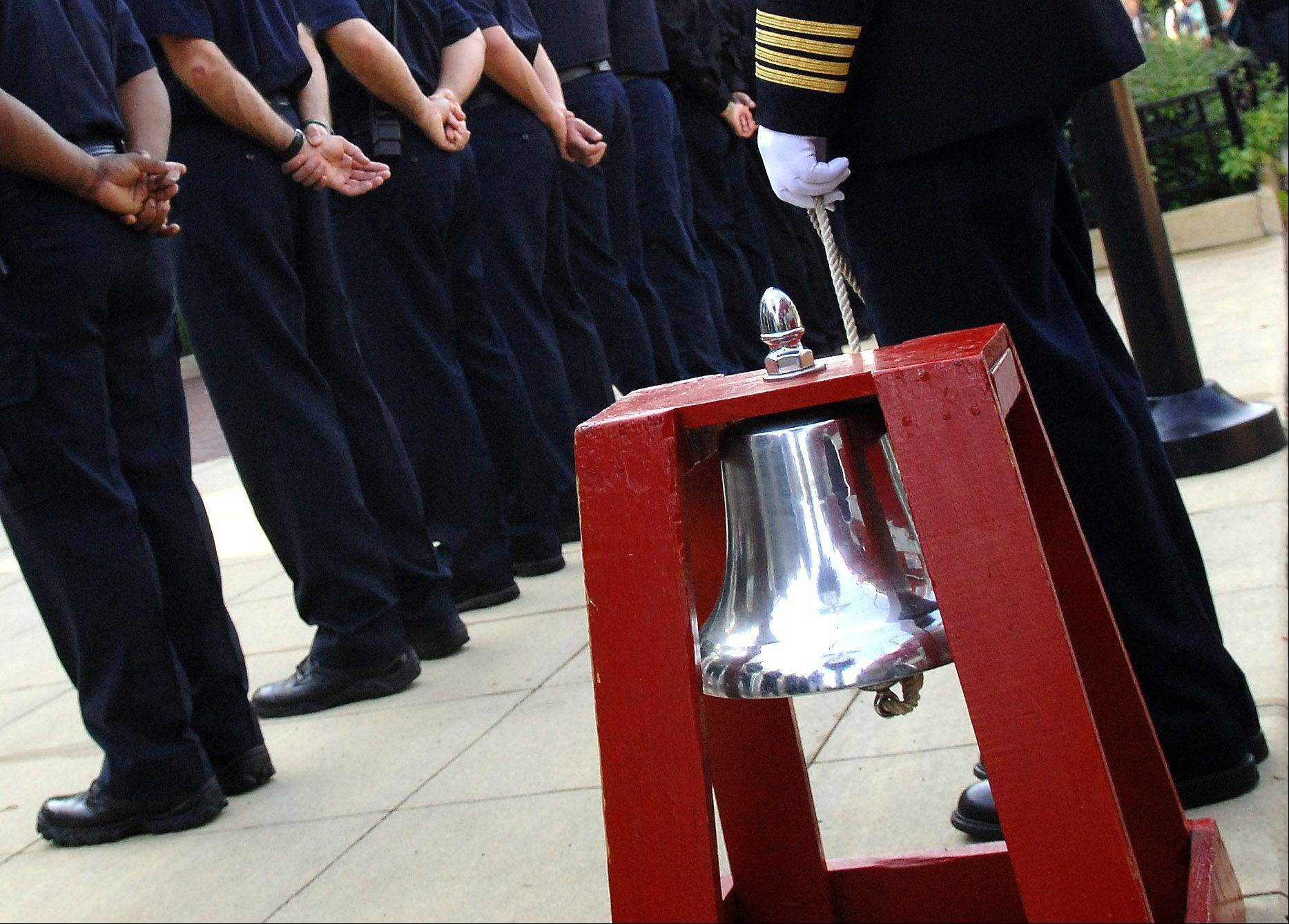 A fire house bell is rung in honor of the firefighters who lost their lives in the aftermath of the terrorist attacks of 2001 during the city of Elgin's Sept. 11th ceremony in front of the police department building Wednesday.
