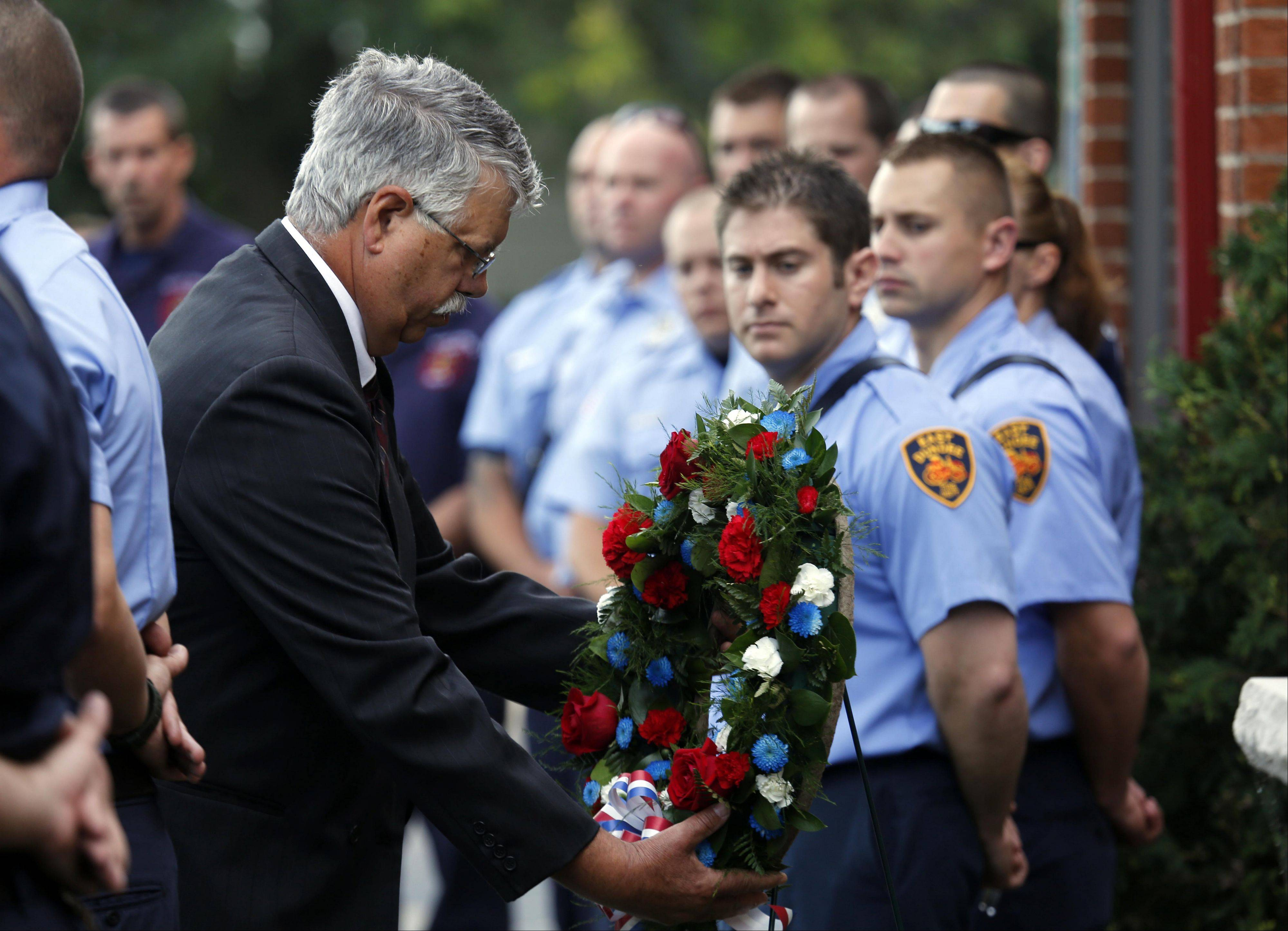 "Carpentersville Village President Ed Ritter places a wreath on a stand while ""Amazing Grace"" plays Wednesday morning during a Sept. 11 remembrance ceremony at Fire Station 1."