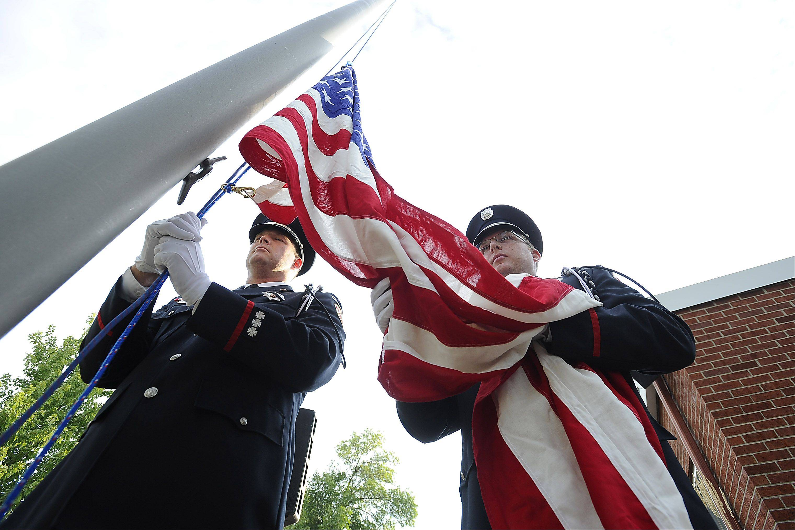 "Kevin Jones, right, and Jeff Gove of the Des Plaines Fire Department prepare to raise the colors at the Sept. 11 ""Patriot Day"" ceremony at Fire Station No. 1 on Wednesday."